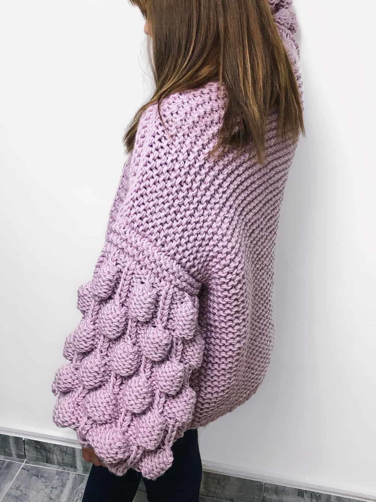 На третьей фотографии женский фиолетовый кардиган сбоку от Shapar, бренда вязаной одежды ручной работы в интернет-магазине связанных спицами вещей.