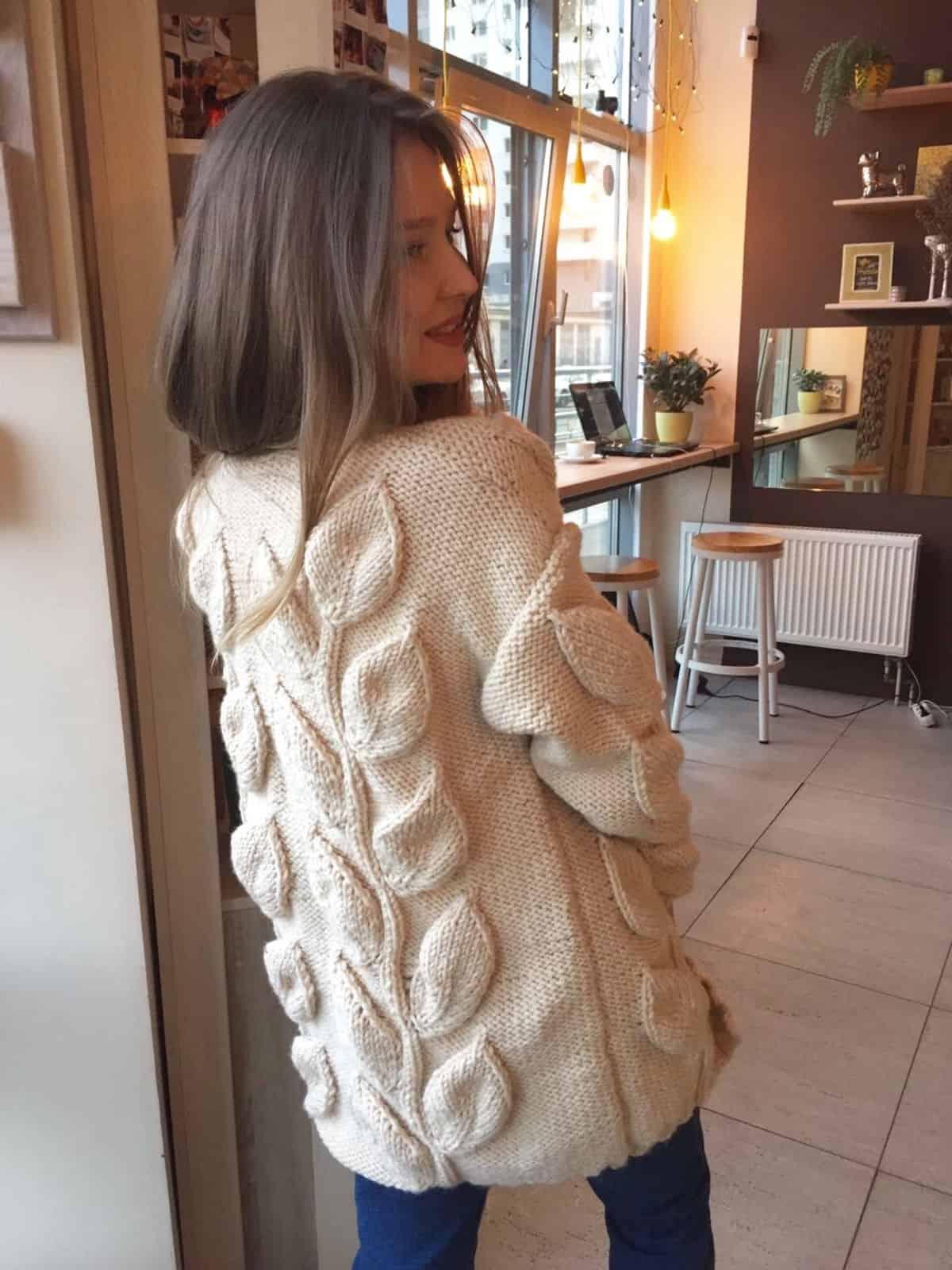 На фотографии женский кардиган с листьями от SHAPAR, бренда вязаной одежды ручной работы в интернет-магазине связанных спицами вещей.