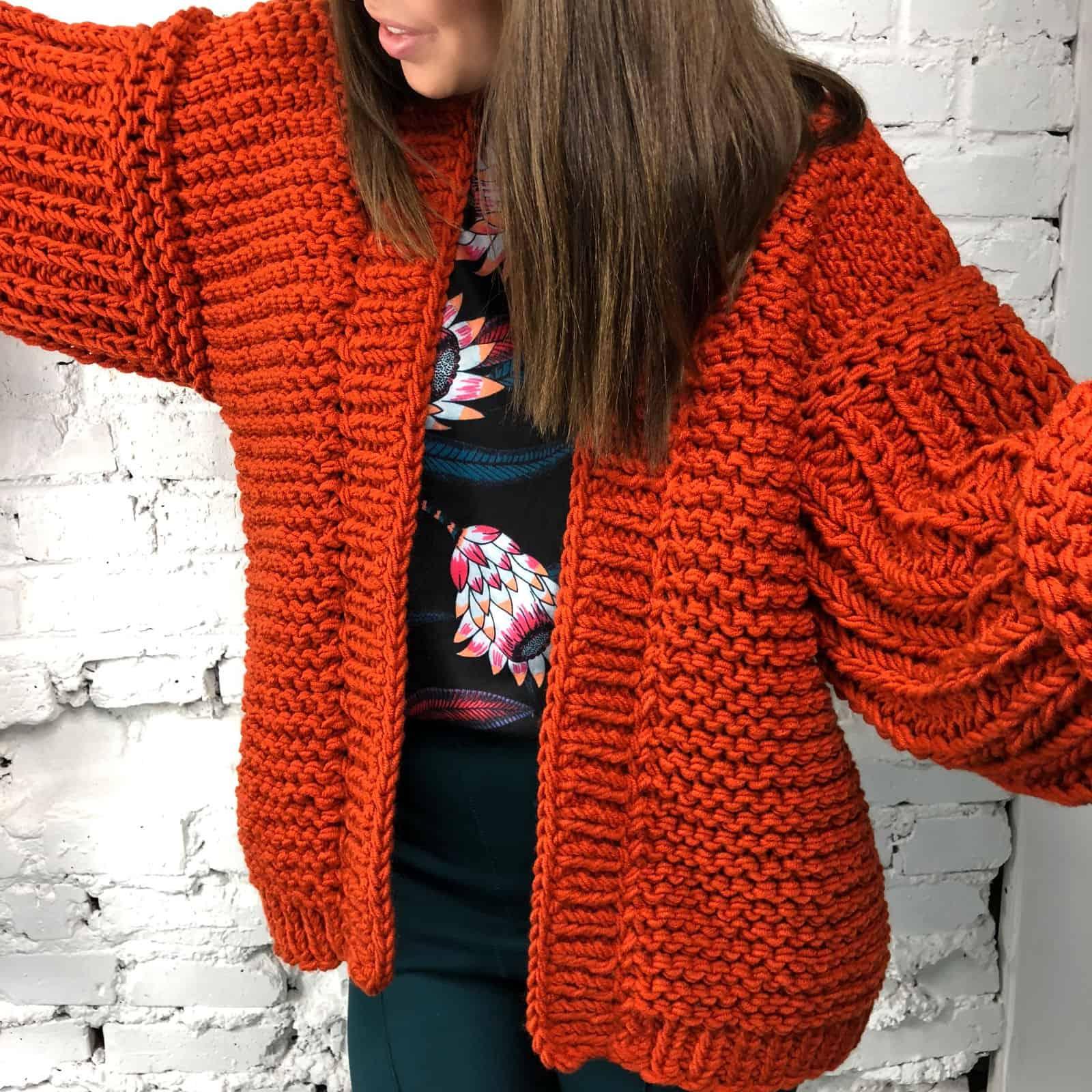 На третьей фотографии женский коралловый кардиган крупной вязки от Shapar, бренда вязаной одежды ручной работы в интернет магазине связанных спицами вещей.