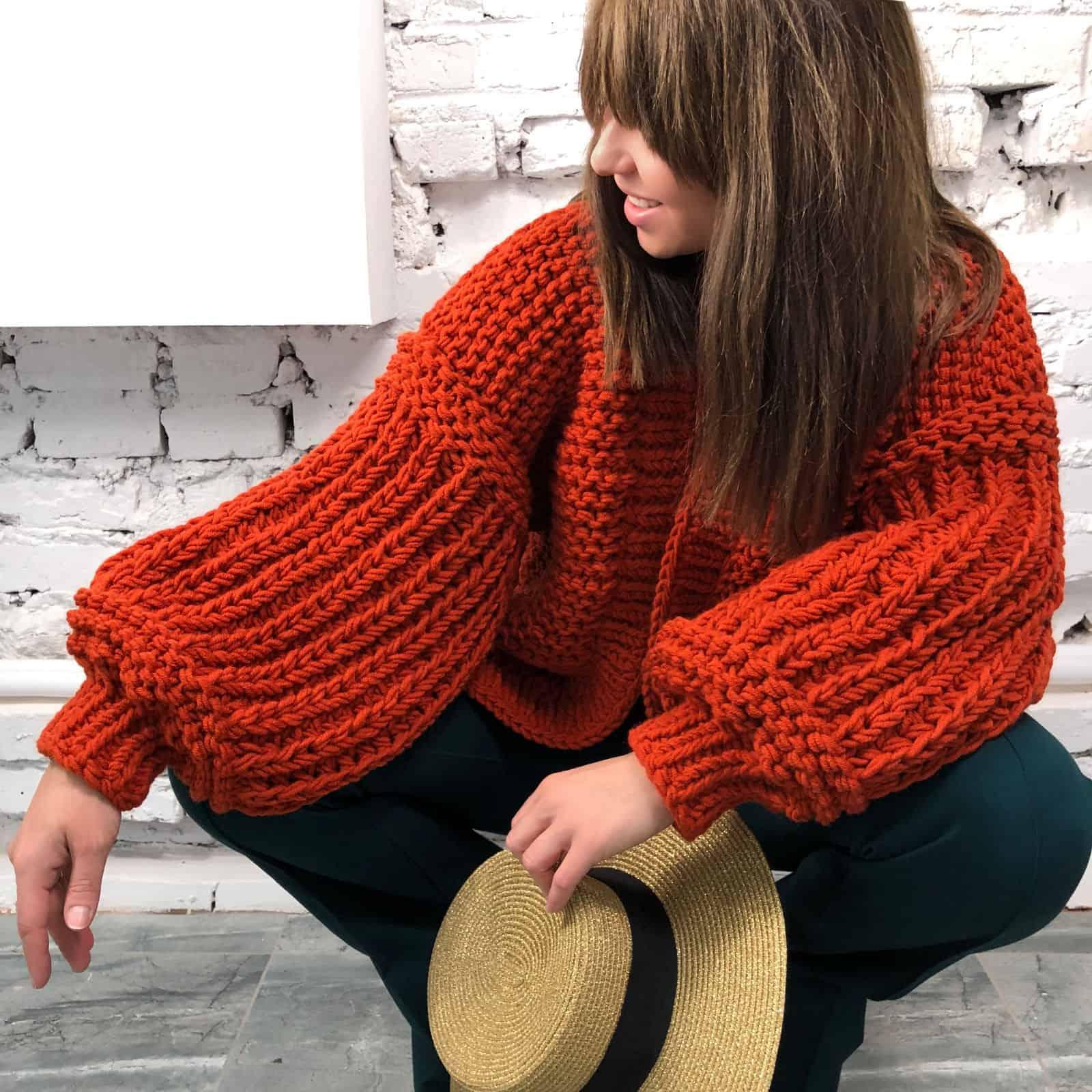 На фотографии женский коралловый кардиган от Shapar, бренда вязаной одежды ручной работы в интернет магазине связанных спицами вещей.