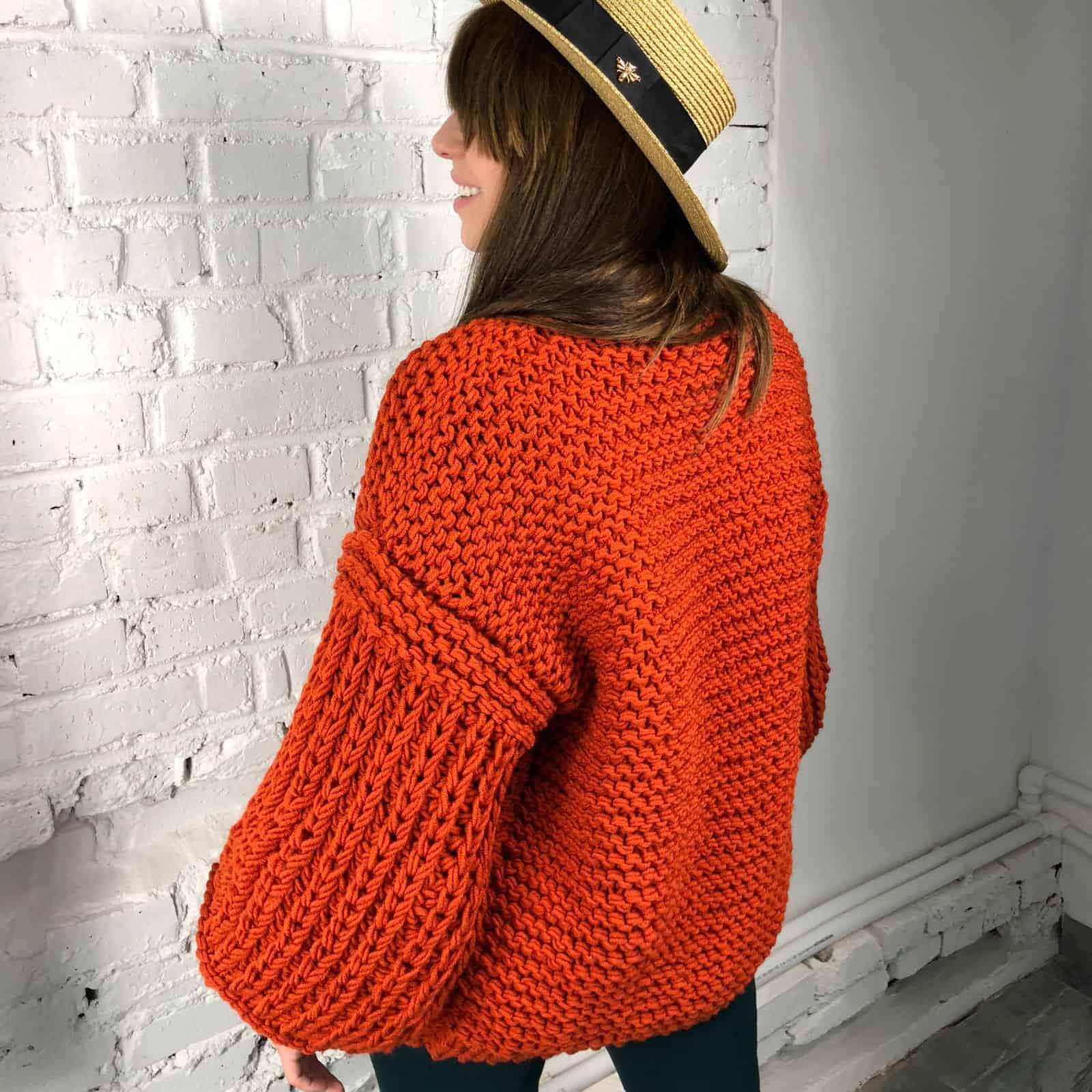 На второй фотографии женский коралловый кардиган со спины от Shapar, бренда вязаной одежды ручной работы в интернет магазине связанных спицами вещей.