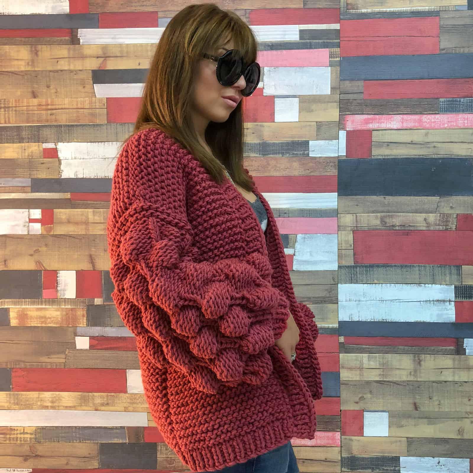 На фотографии короткий вязаный кардиган от SHAPAR, бренда женской одежды ручной работы в интернет магазине связанных спицами вещей.