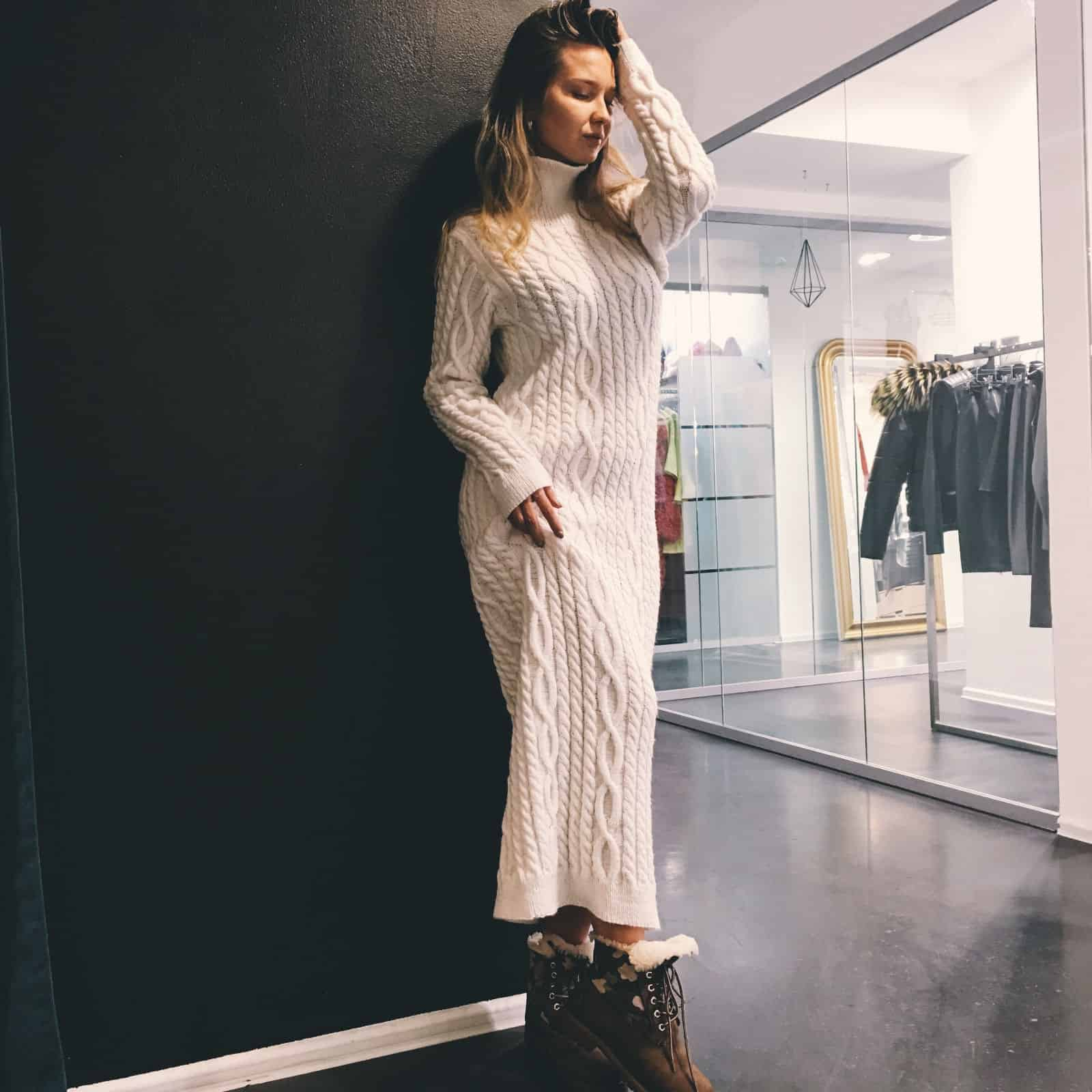 На фотографии белое длинное вязаное платье с косами от SHAPAR, бренда эксклюзивной женской одежды ручной работы в интернет-магазине платьев и связанных спицами вещей.