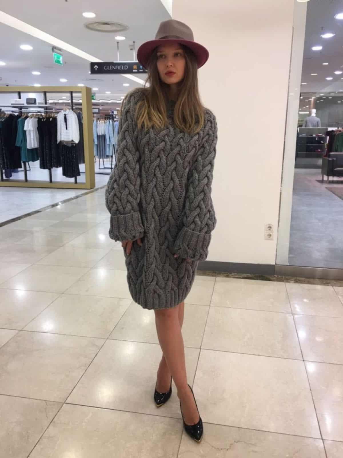 На фотографии женский длинный свитер крупной вязки от SHAPAR, бренда одежды ручной работы в интернет-магазине связанных спицами вещей.