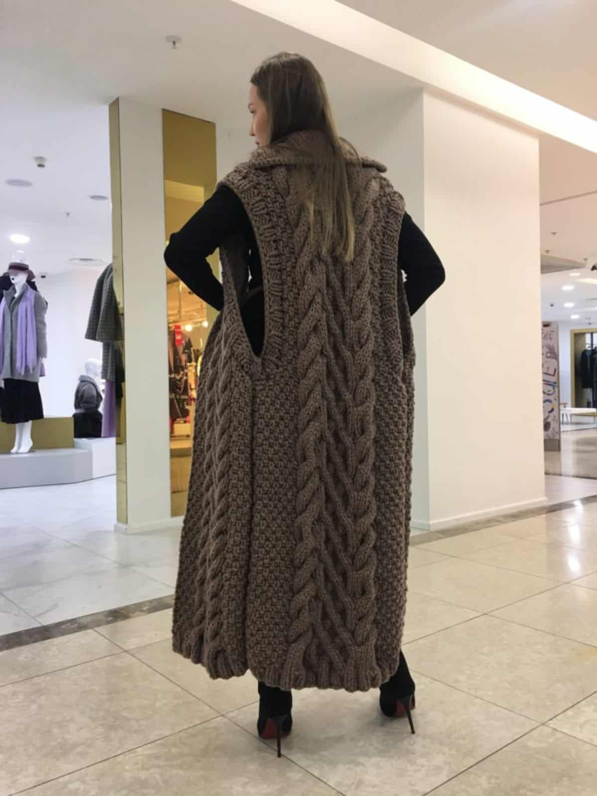 На фотографии женский длинный жилет с косами коричневого цвета от SHAPAR, бренда вязаной одежды ручной работы в интернет-магазине связанных спицами вещей.