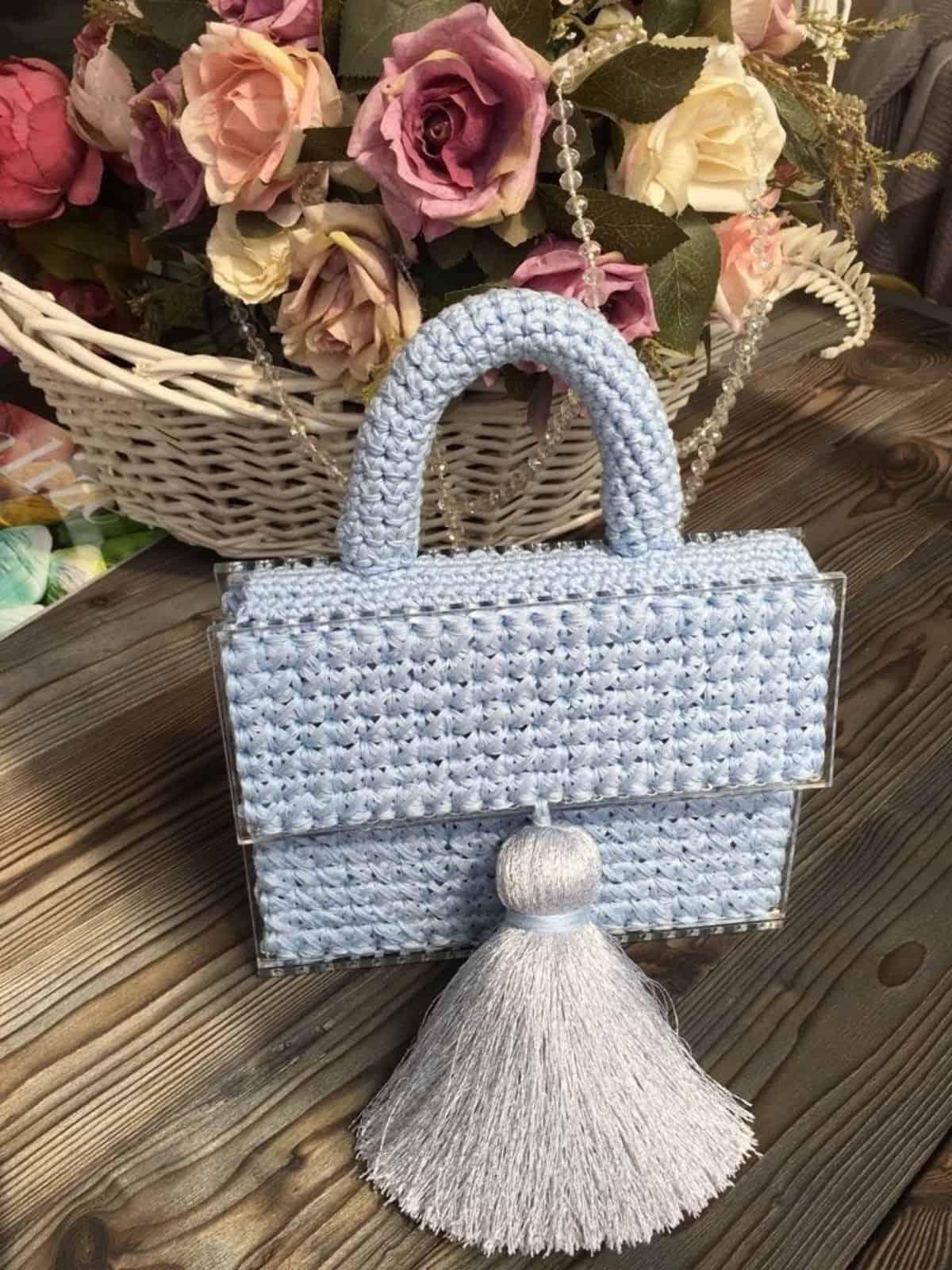 На фотографии изысканная голубая сумка от SHAPAR, бренда женских вязаных аксессуаров ручной работы в интернет-магазине связанных спицами вещей.