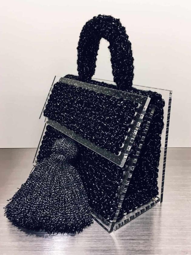 На фотографии женская маленькая черная сумка от Shapar, бренда вязаной одежды и аксессуаров ручной работы в интернет-магазине связанных спицами вещей.
