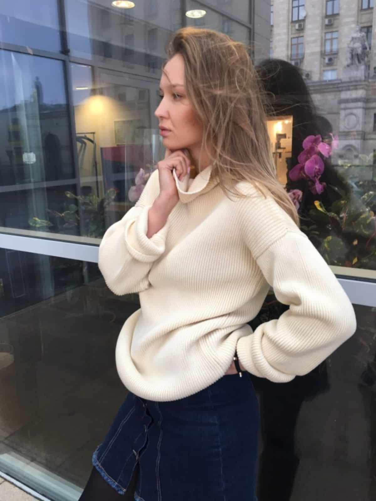 На фотографии молочный вязаный свитер от SHAPAR, бренда женской одежды ручной работы в интернет-магазине связанных спицами вещей.