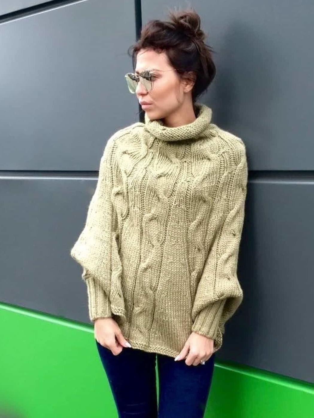На фотографии женское оливковое пончо от Shapar, бренда вязаной одежды ручной работы в интернет-магазине связанных спицами вещей.