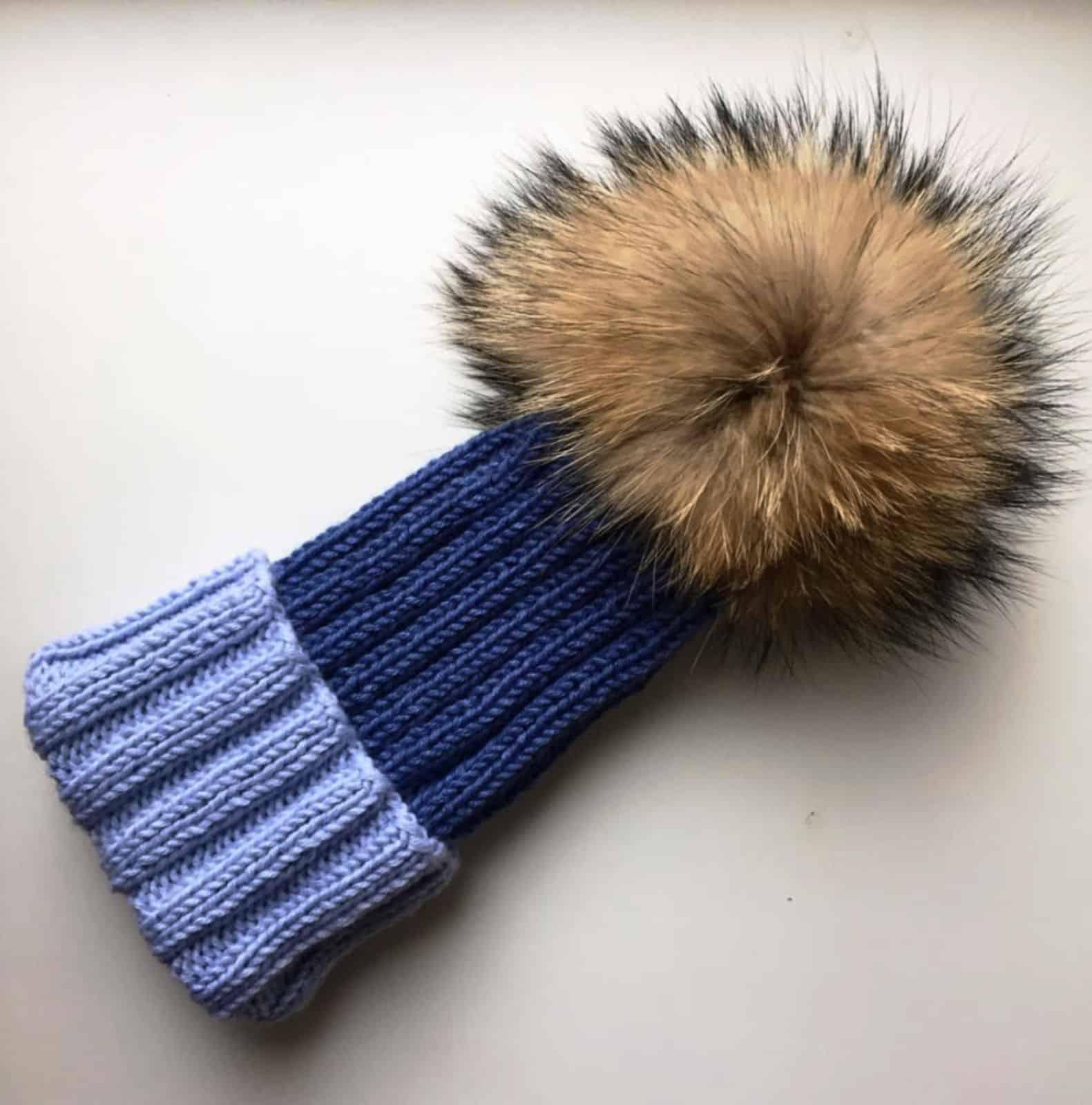 На фотографии синяя шапка с меховым помпоном от SHAPAR, бренда вязаной одежды ручной работы в интернет-магазине связанных спицами вещей.