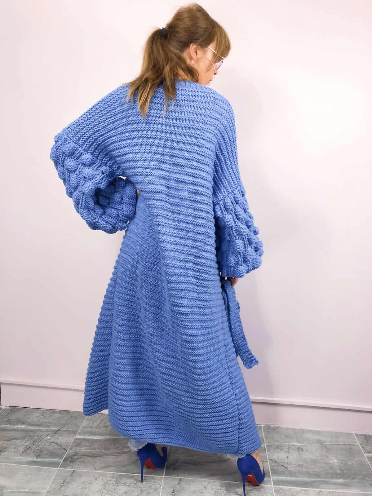 На фотографии современный женский кардиган синего цвета от SHAPAR, бренда вязаной одежды ручной работы в интернет-магазине связанных спицами вещей.