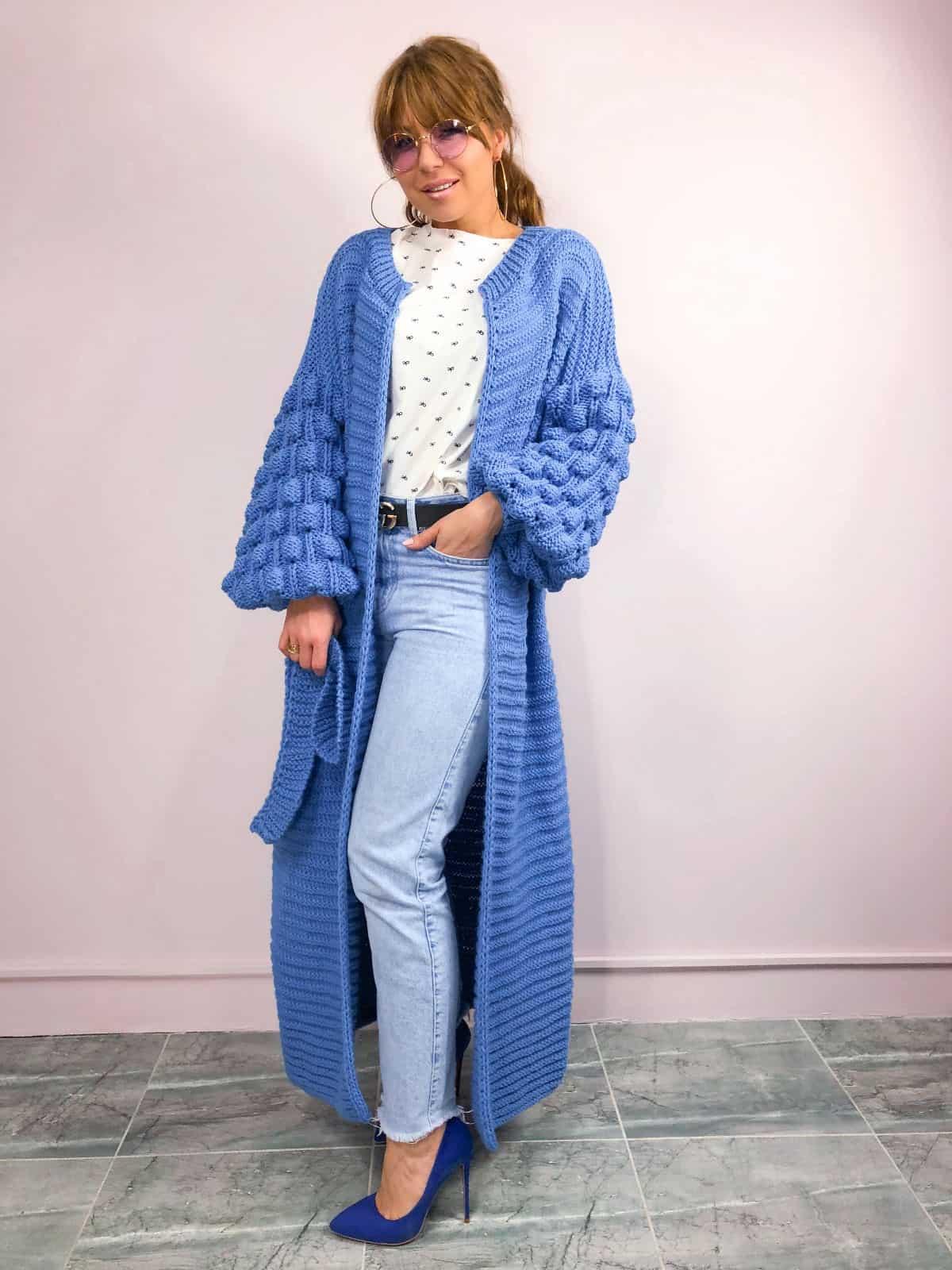 На фотографии женский современный кардиган синего цвета от Shapar, бренда вязаной одежды ручной работы в интернет-магазине связанных спицами вещей.