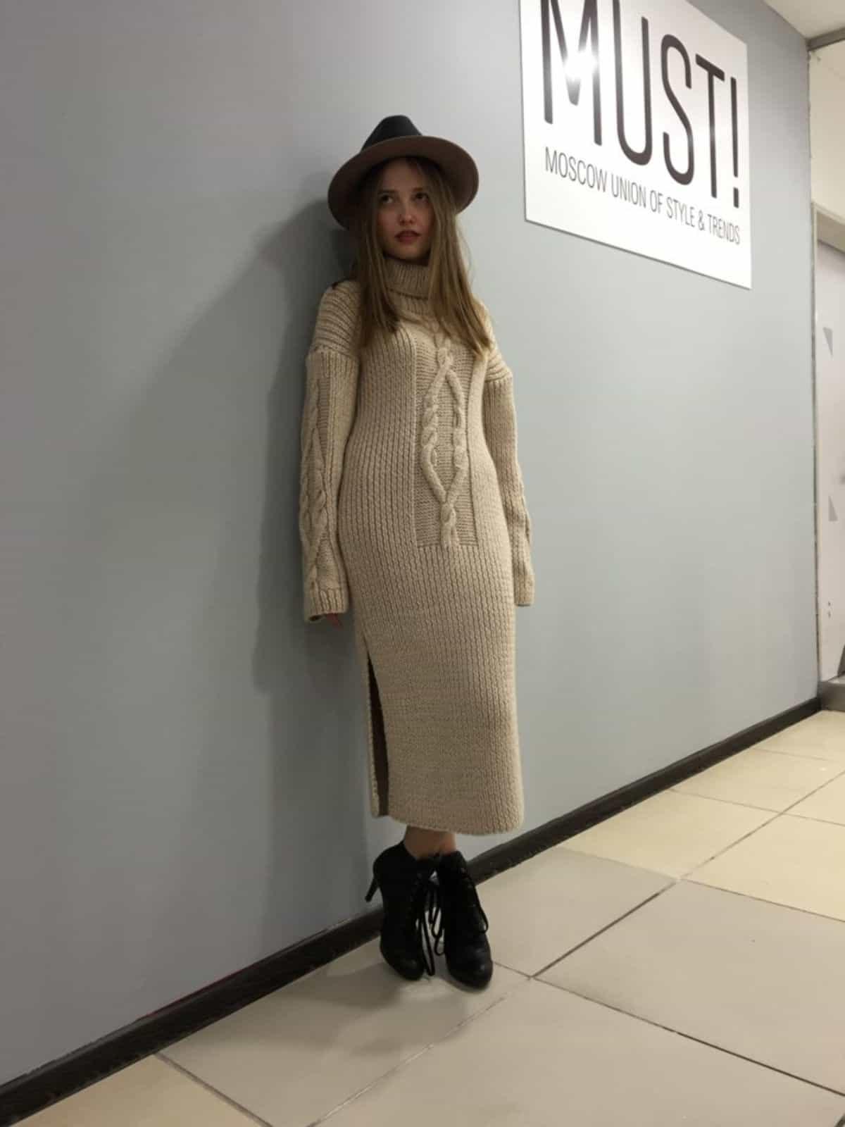 На фотографии стильное вязаное платье с косой в бежевом цвете от SHAPAR, бренда  женской одежды ручной работы в интернет-магазине связанных спицами вещей.