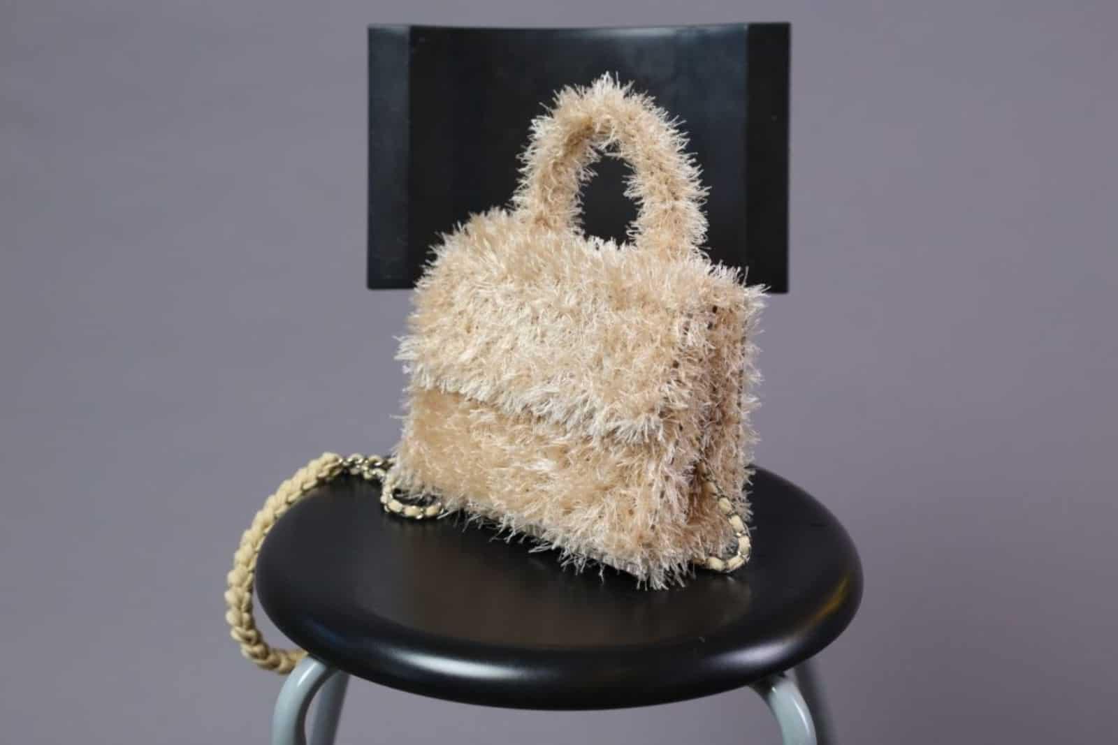На фотографии женская бежевая сумка ручной работы от SHAPAR, бренда вязаных аксессуаров в интернет-магазине связанных спицами вещей.