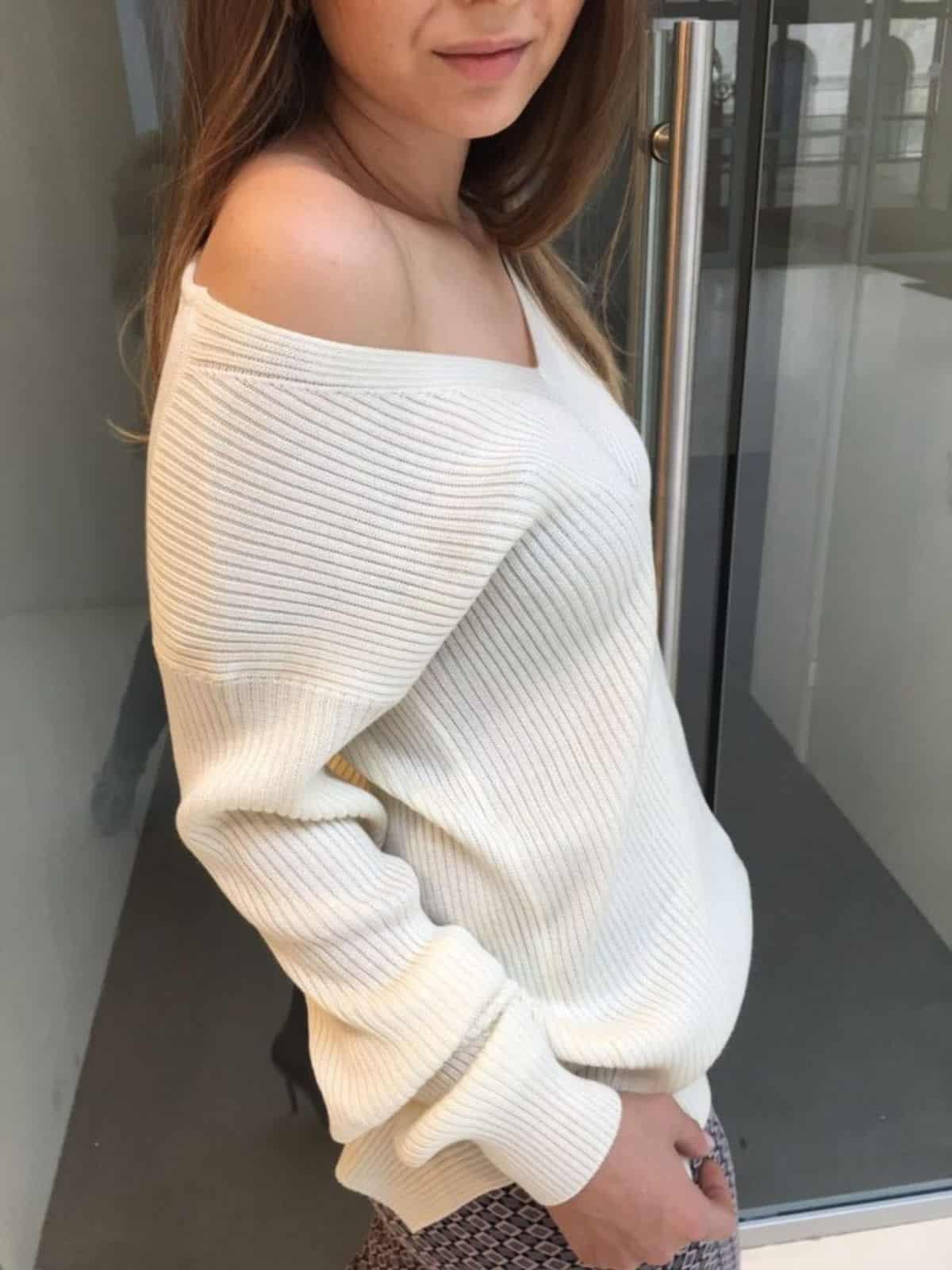 На фотографии стильный белый свитер на одно плечо от SHAPAR, бренда женской вязаной одежды ручной работы в интернет-магазине связанных спицами вещей.