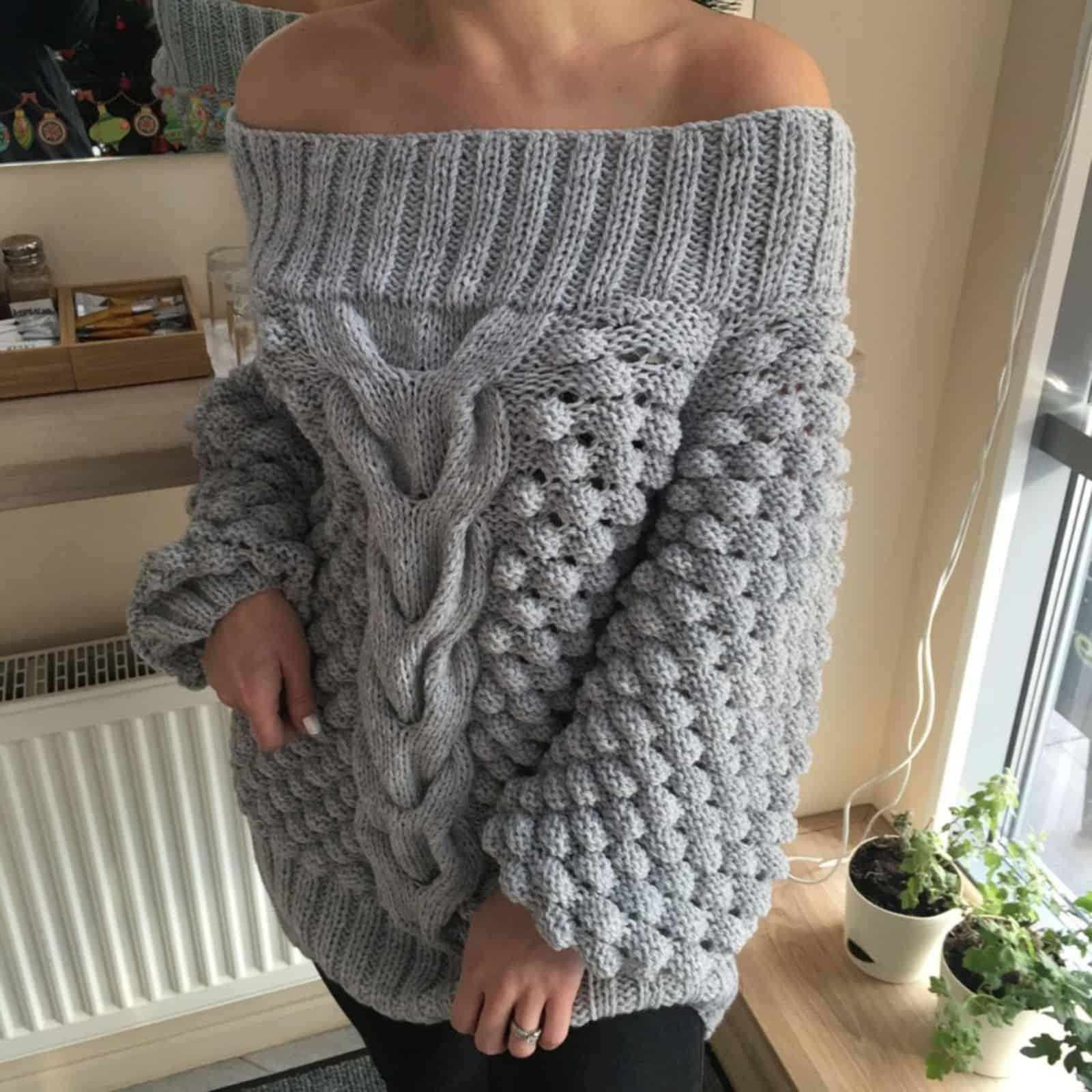 На фотографии женский свитер со спущенным плечом от Shapar, бренда вязаной одежды ручной работы в интернет-магазине связанных спицами вещей.