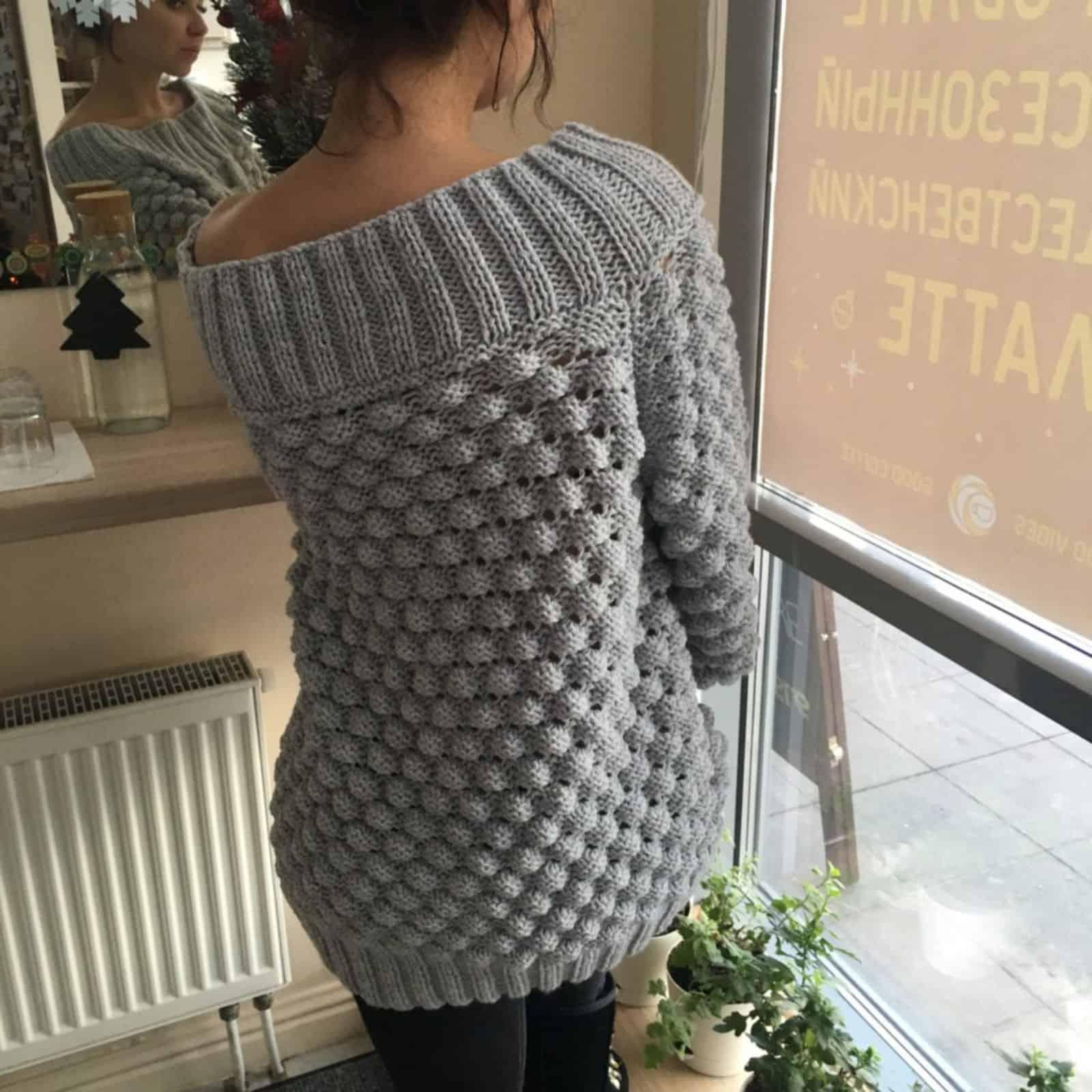 На четвертой фотографии объемный женский свитер со спущенным плечом от Shapar, бренда вязаной одежды ручной работы в интернет-магазине связанных спицами вещей.