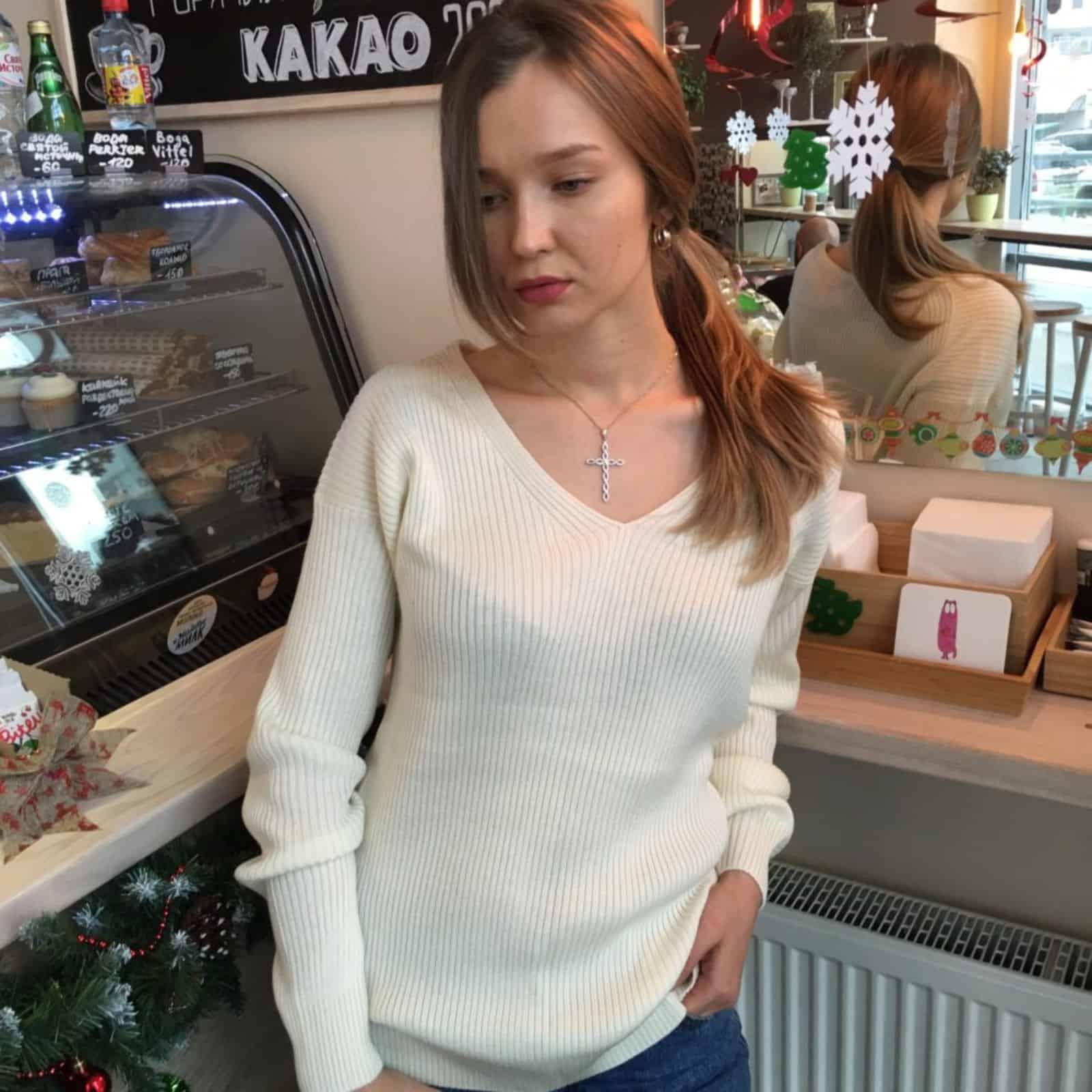 На фотографии молочный тонкий джемпер на одно плечо от SHAPAR, бренда женской вязаной одежды ручной работы в интернет-магазине связанных спицами вещей.