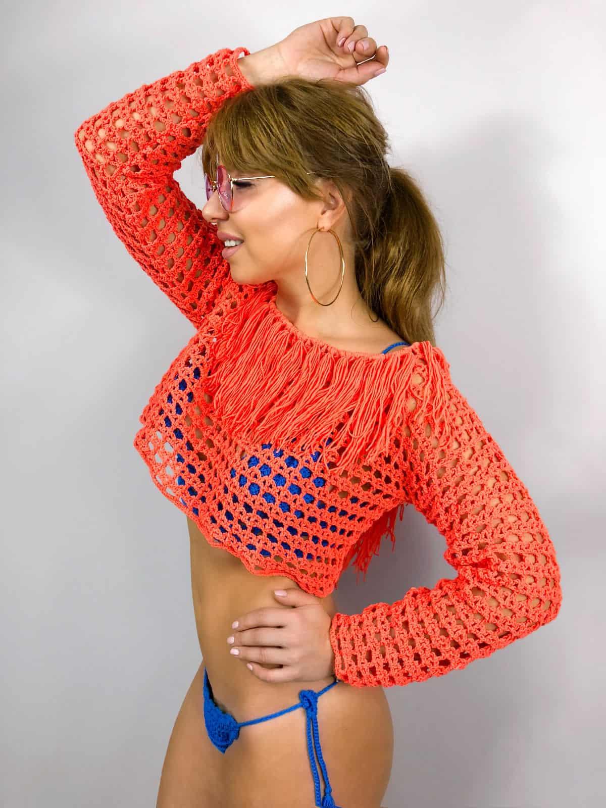 На фотографии женская туника крючком кораллового цвета от SHAPAR, бренда вязаной одежды ручной работы в интернет-магазине связанных вещей.