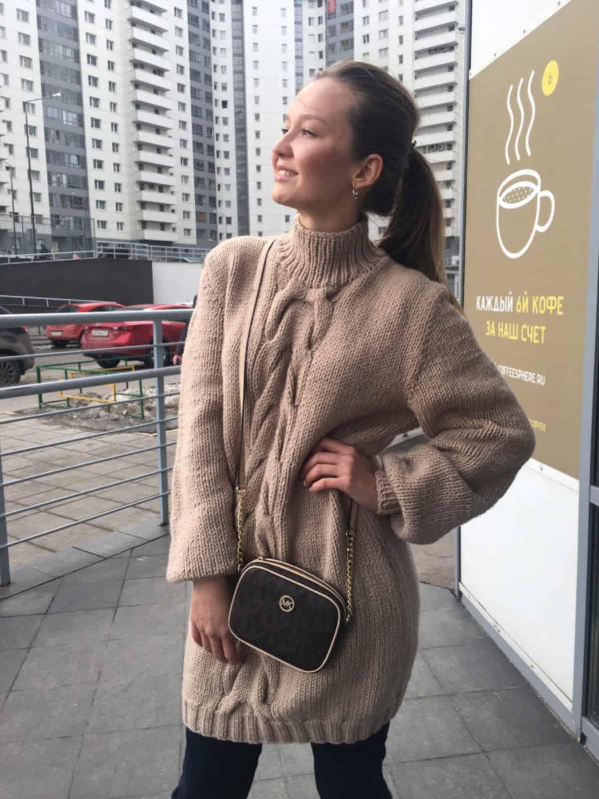 На фотографии вязаный удлиненный свитер с косой от SHAPAR, бренда женской одежды ручной работы в интернет-магазине связанных спицами вещей.