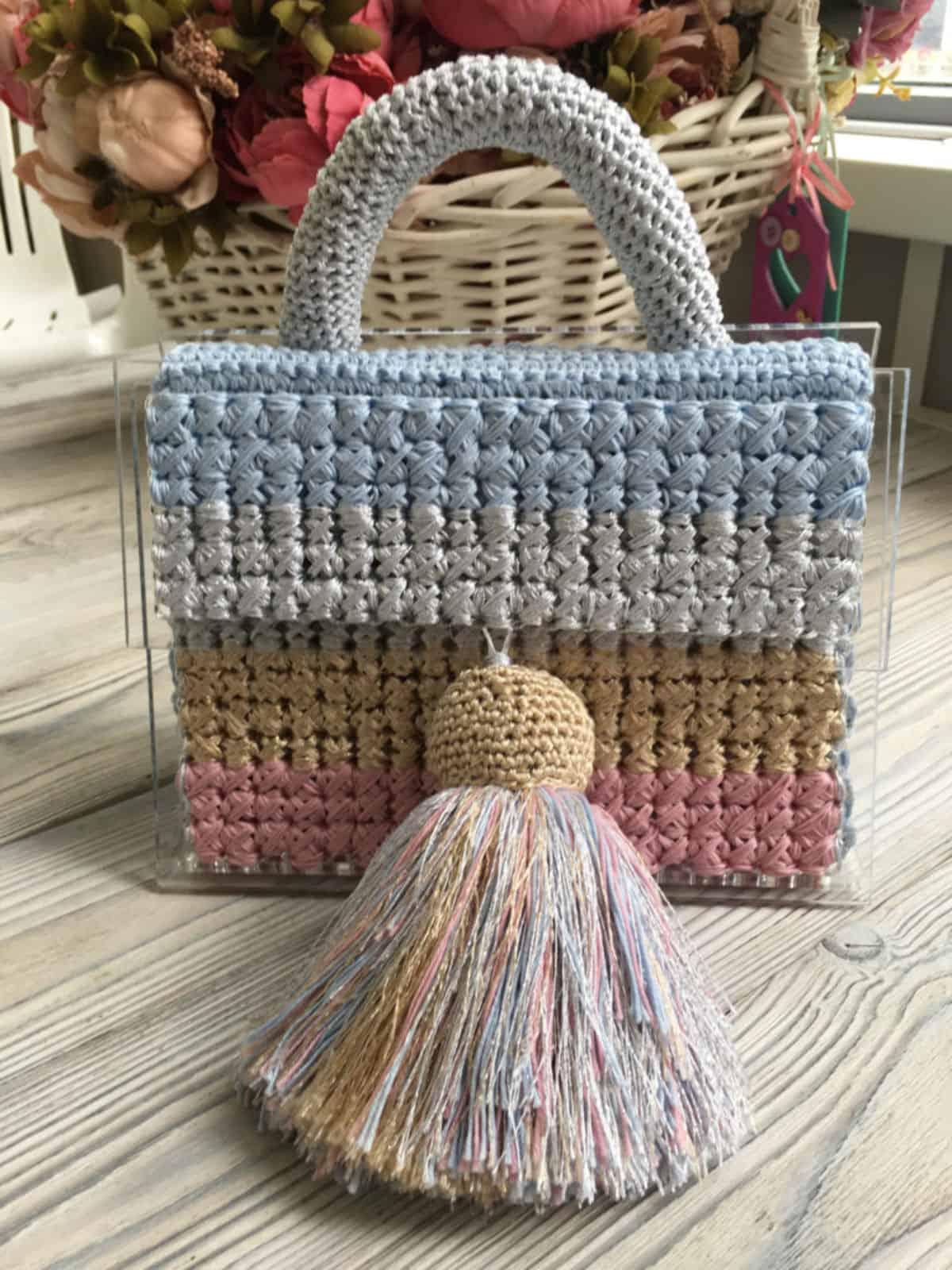 На фотографии женская яркая сумка с прозрачным дном от SHAPAR, бренда вязаных аксессуаров ручной работы в интернет-магазине связанных вещей.
