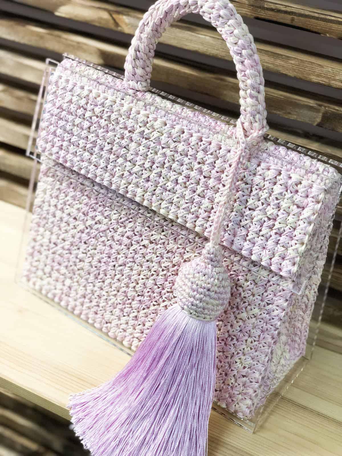 На четвертой фотографии бледно-розовая стеклянная сумка от Shapar, бренда вязаных аксессуаров и одежды ручной работы в интернет магазине связанных спицами вещей.