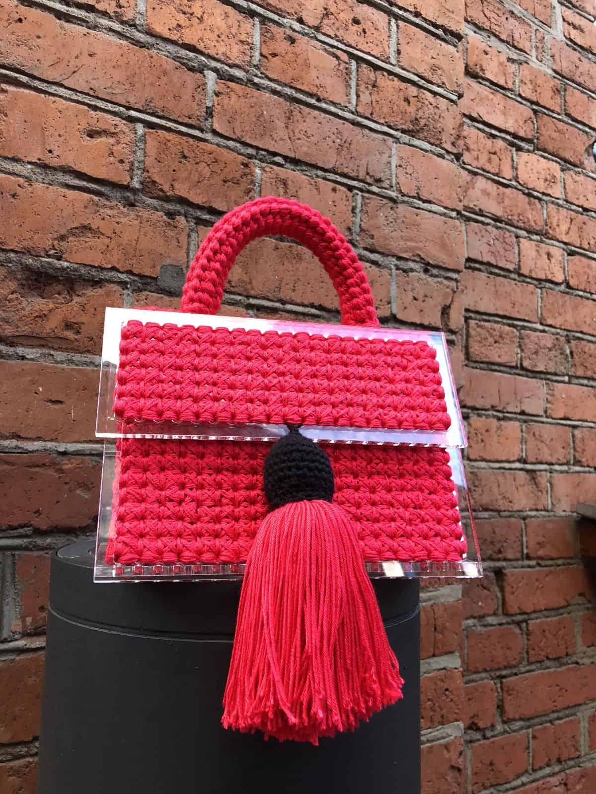 На третьей фотографии маленькая красная сумка с кистью от Shapar, бренда вязаных вещей и аксессуаров ручной работы в интернет-магазине связанной спицами одежды.