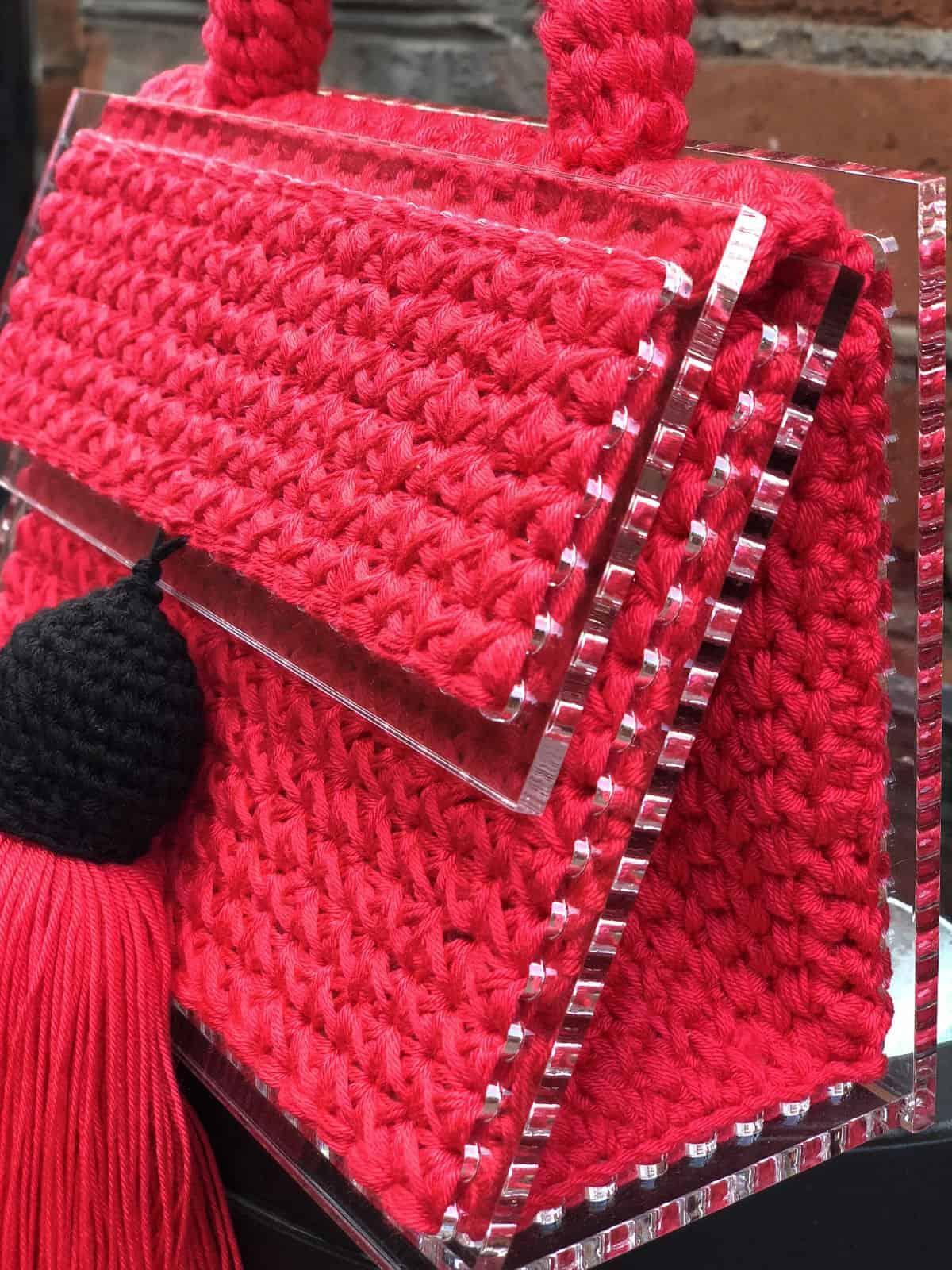 На четвертой фотографии маленькая красная сумка из оргстекла от Shapar, бренда вязаных вещей и аксессуаров ручной работы в интернет-магазине связанной спицами одежды.