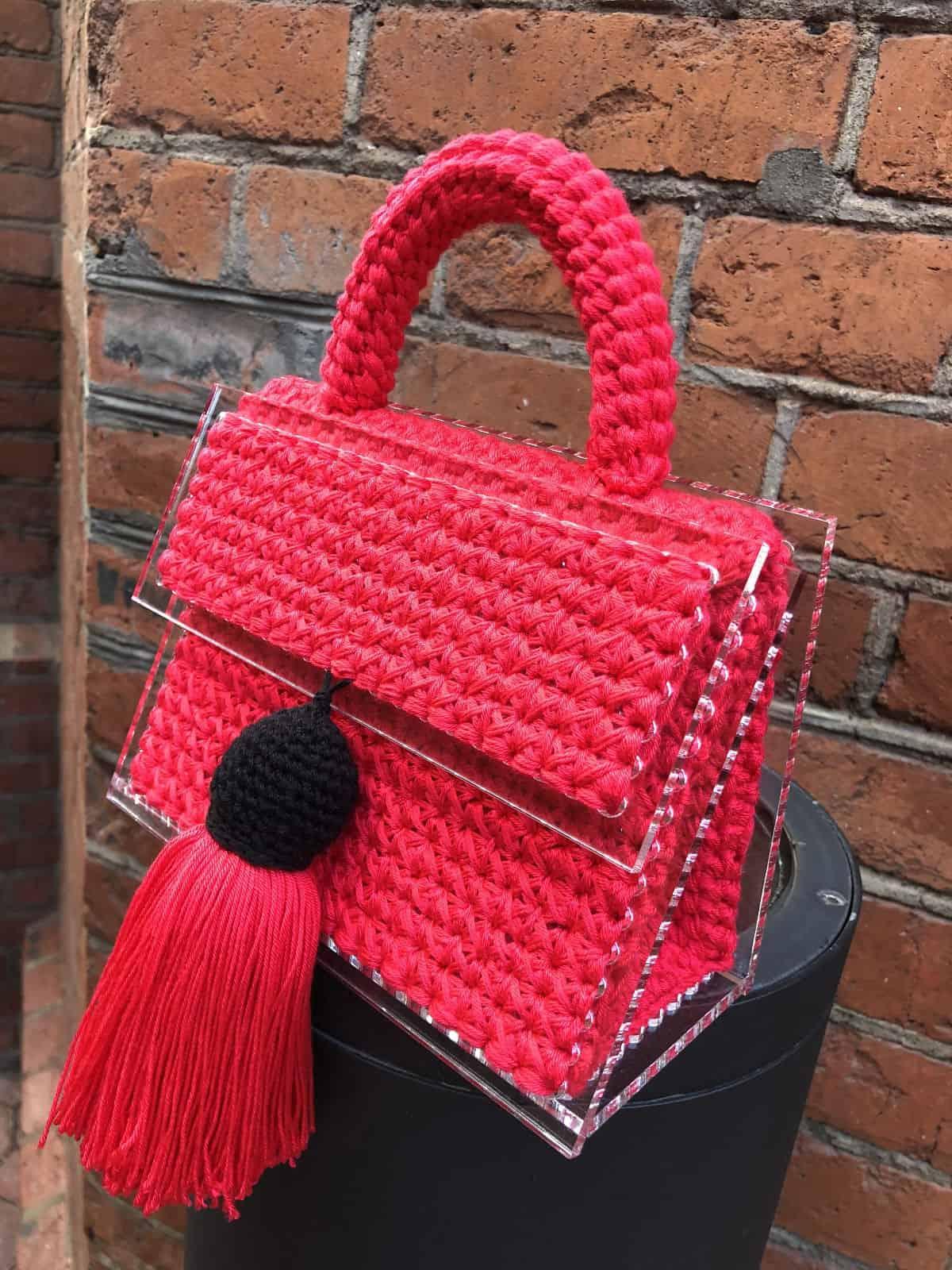 На пятой фотографии маленькая женская сумка красного цвета с прозрачным дном от Shapar, бренда вязаных вещей и аксессуаров ручной работы в интернет-магазине связанной спицами одежды.
