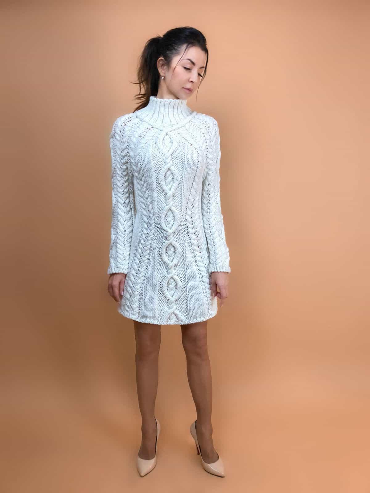 На фотографии вязаное белое платье с косами от Shapar, бренда одежды ручной работы в интернет-магазине связанных спицами вещей.