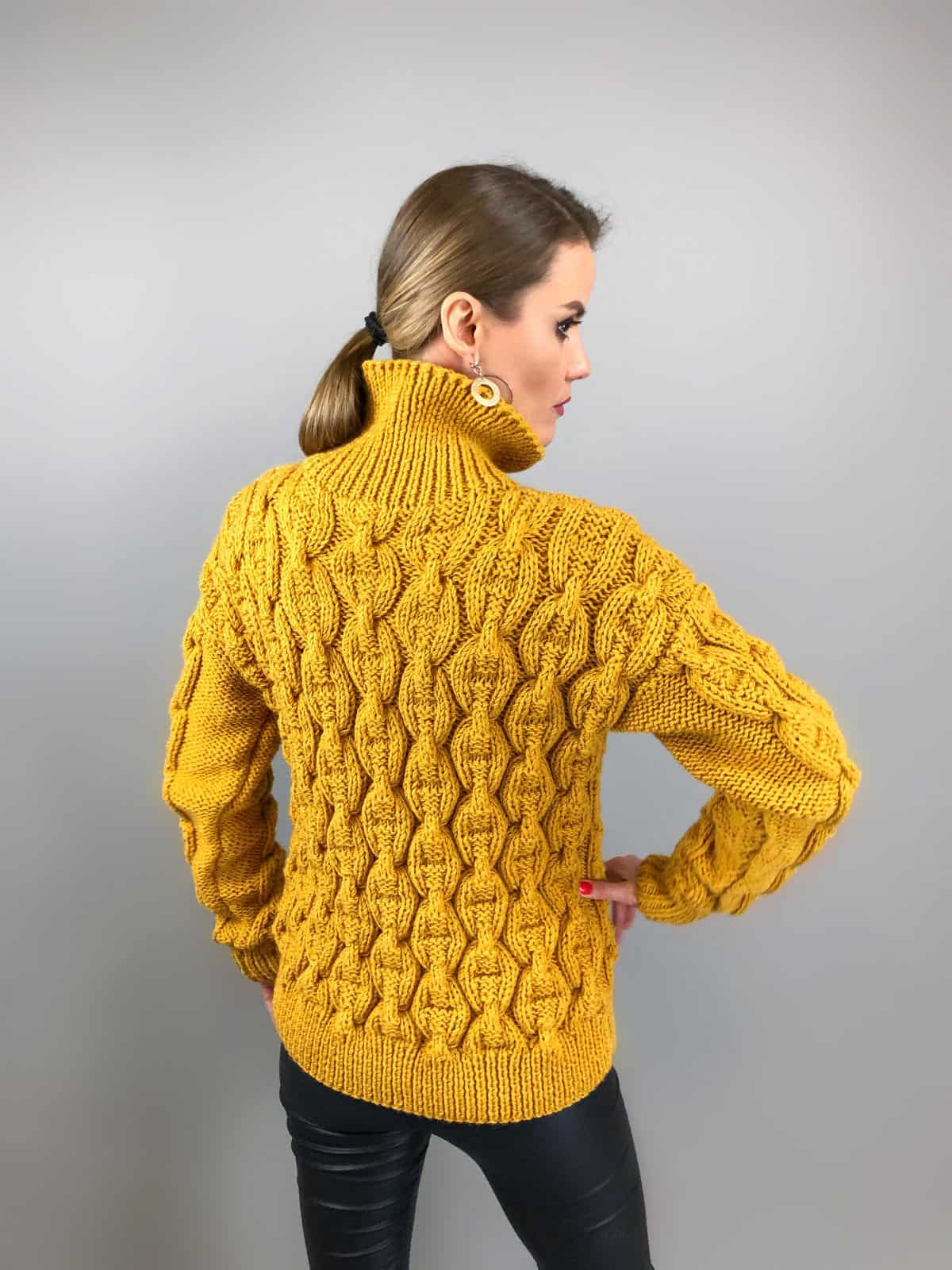 На второй фотографии горчичный свитер цепи со спины от Shapar, бренда вязаной одежды ручной работы в интернет-магазине связанных спицами вещей.