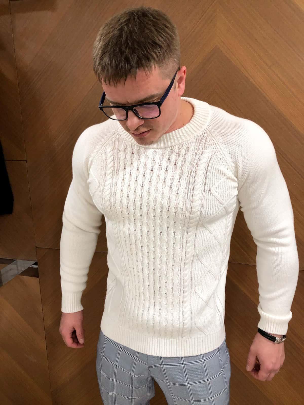 На фотографии белый свитер с косами для мужчин от Shapar, бренда вязаной одежды ручной работы в интернет-магазине связанных спицами вещей.