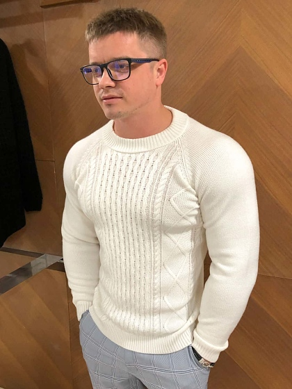 На фотографии мужской свитер белый с косами от Shapar, бренда вязаной одежды ручной работы в интернет-магазине связанных спицами вещей.