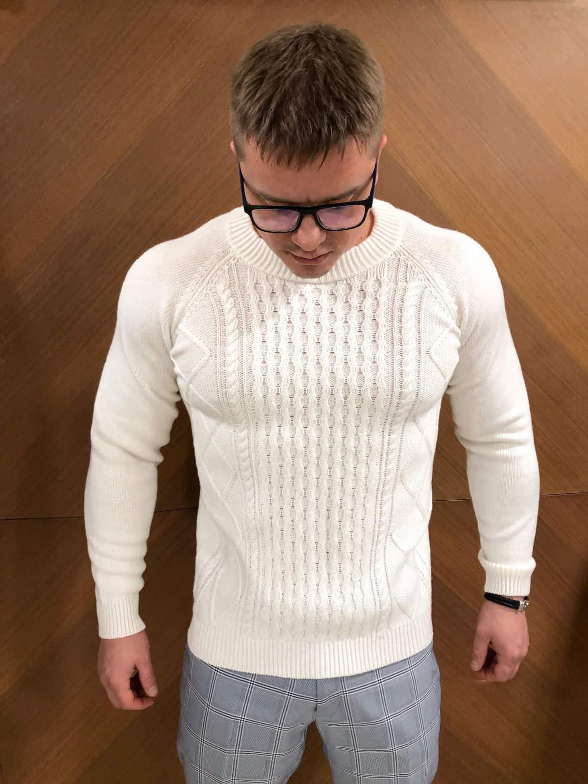 На фотографии модный мужской свитер белый с косами от Shapar, бренда вязаной одежды ручной работы в интернет-магазине связанных спицами вещей.
