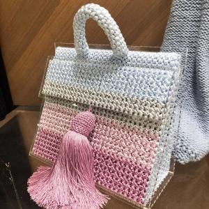 На фотографии женская вязаная сумка от Shapar, бренда вещей и аксессуаров ручной работы в интернет-магазине связанной спицами одежды.