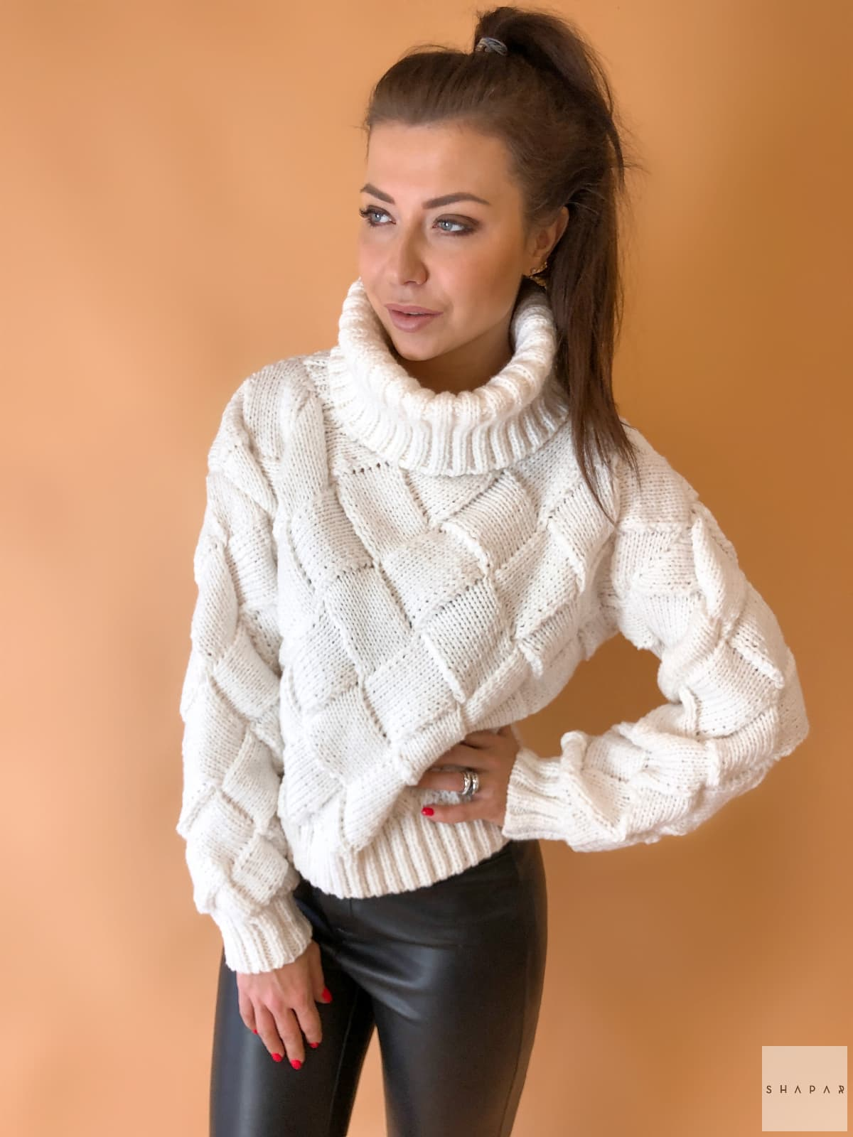 На фотографии женский свитер с высоким горлом от Shapar, бренда вязаной одежды ручной работы в интернет-магазине связанных спицами вещей.
