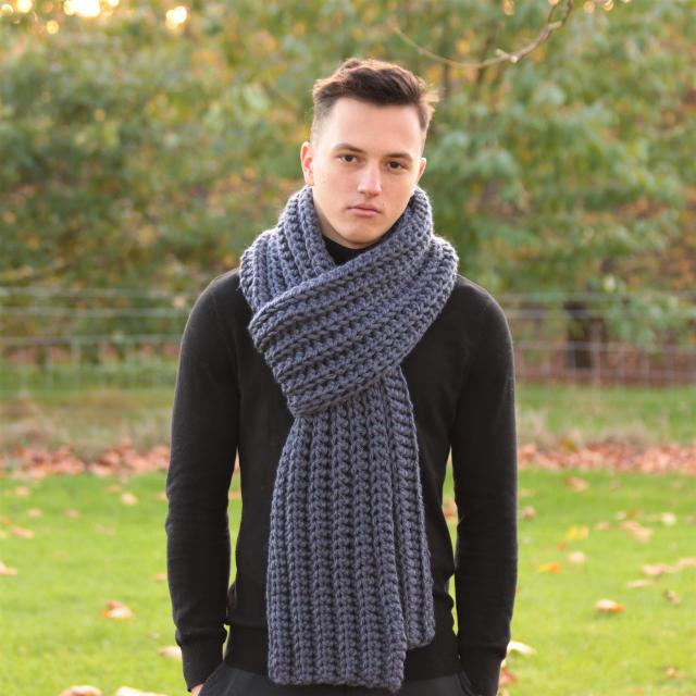 На фотографии серый шарф мужской от Shapar, бренда вязаной одежды ручной работы в интернет-магазине связанных спицами вещей.