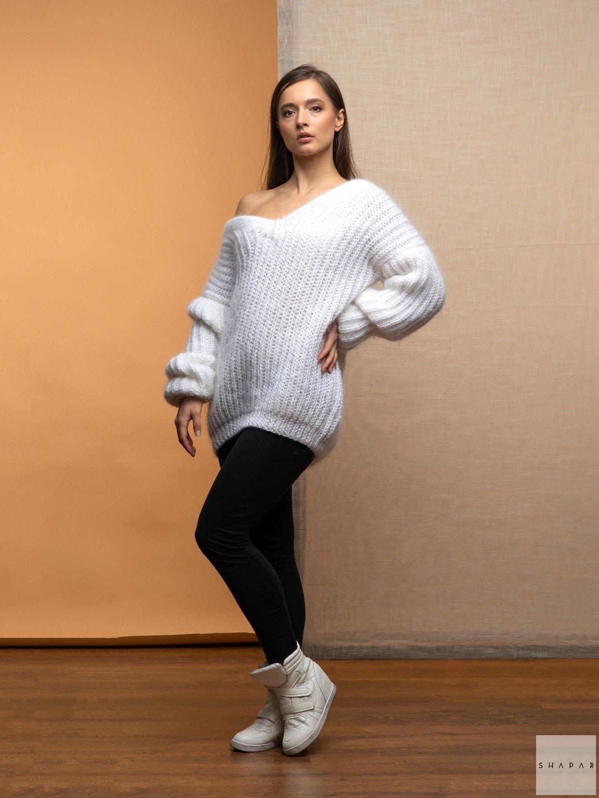 На фотографии белый вязаный свитер от Shapar, бренда женской одежды ручной работы в интернет-магазине связанных спицами вещей.