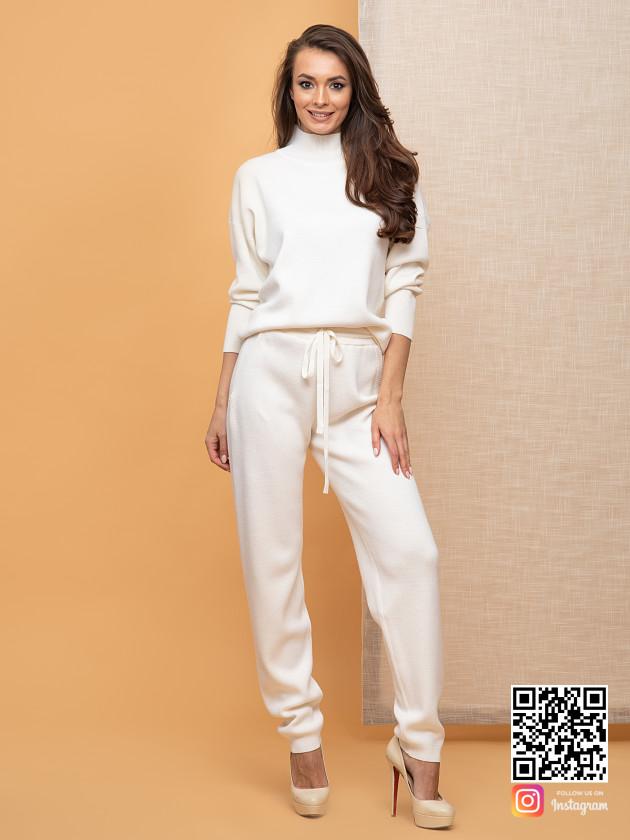 На фотографии белый брючный костюм женский от Shapar, бренда вязаной одежды ручной работы в интернет-магазине связанных спицами вещей.