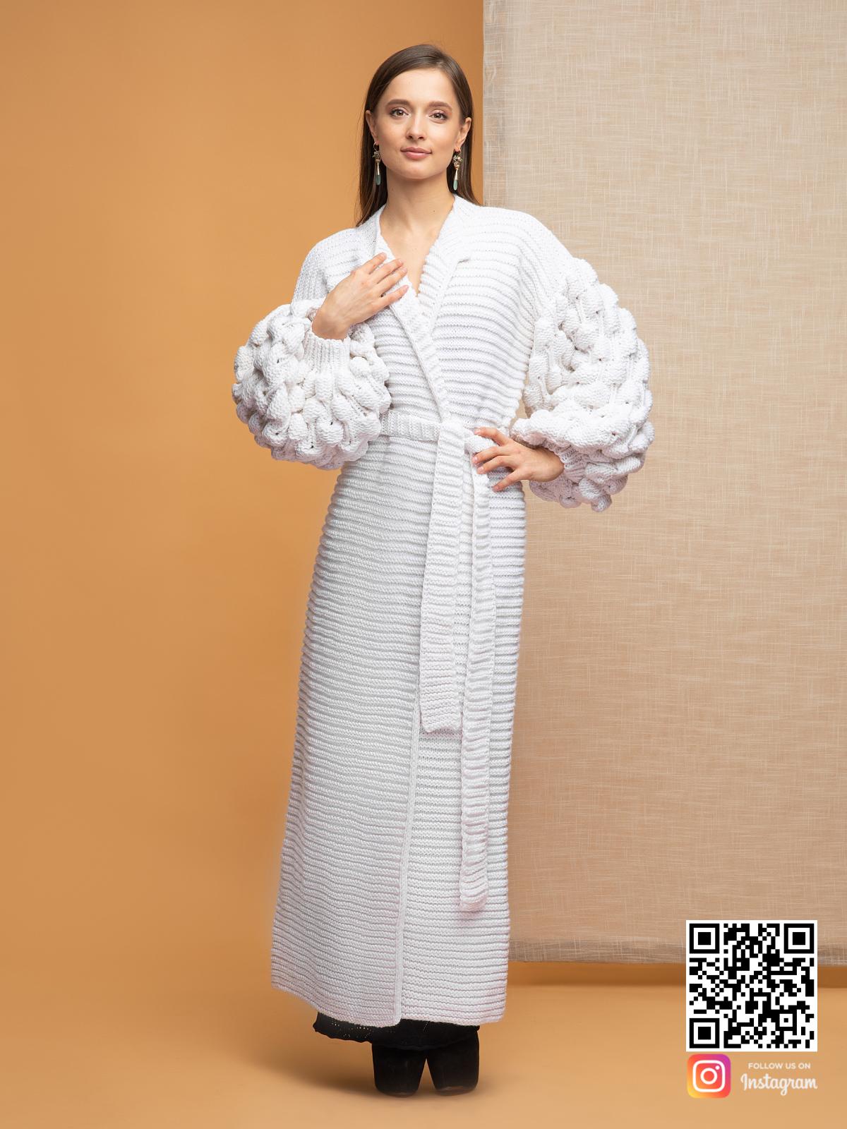 На фотографии белый длинный кардиган женский с объемными рукавами от Shapar, бренда вязаной одежды ручной работы в интернет-магазине связанных спицами вещей.