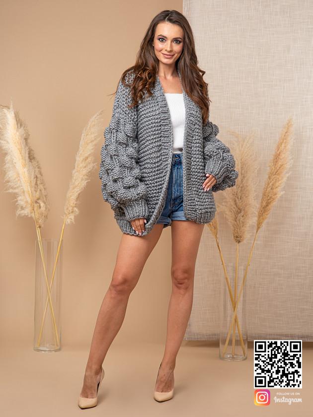 На фотографии кардиган с объемными рукавами от Shapar, бренда вязаной одежды ручной работы в интернет-магазине связанных спицами вещей.