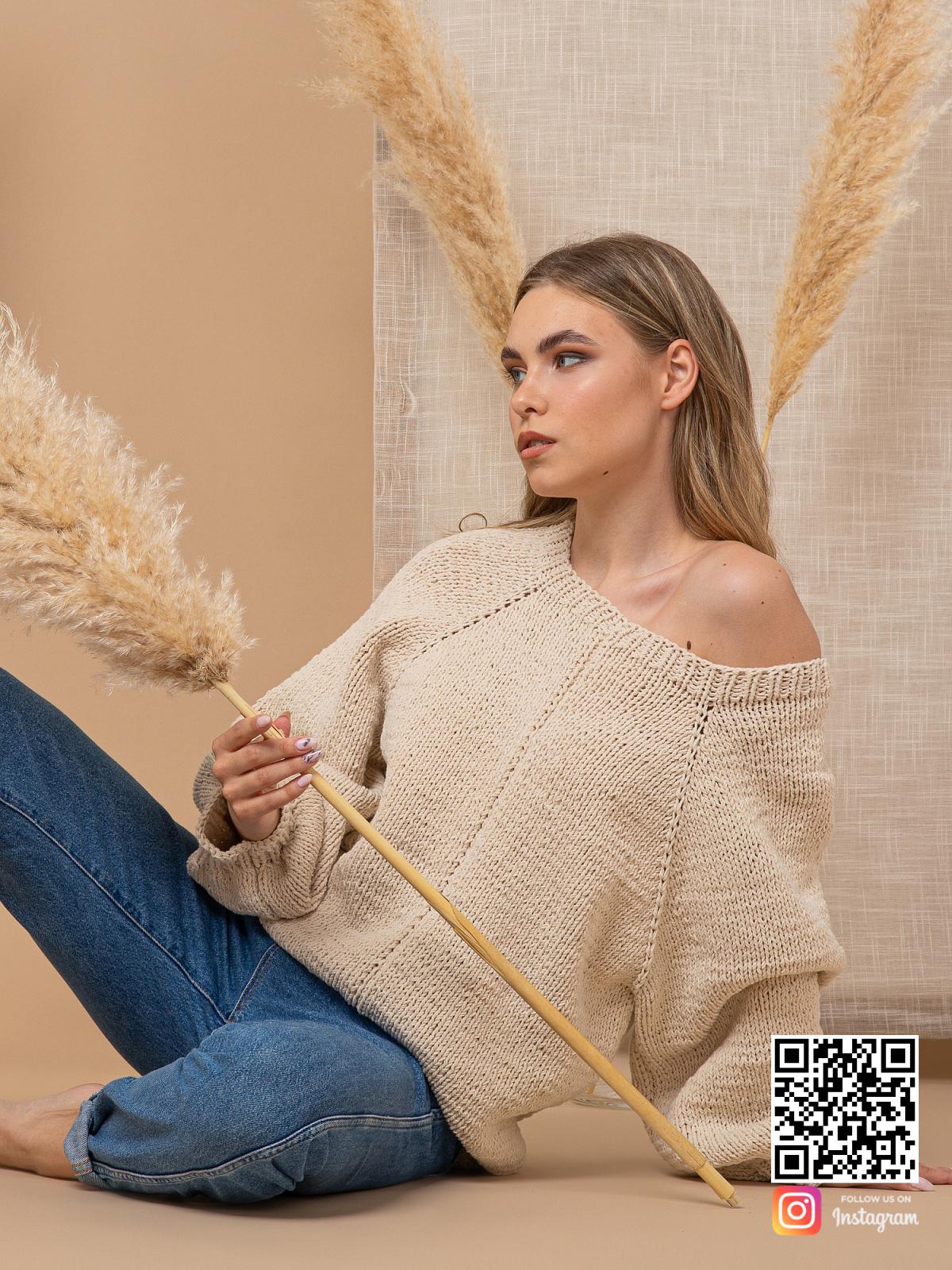 На фотографии женский свитер с открытым плечом спицами от Shapar, бренда вязаной одежды ручной работы в интернет-магазине связанных вещей.