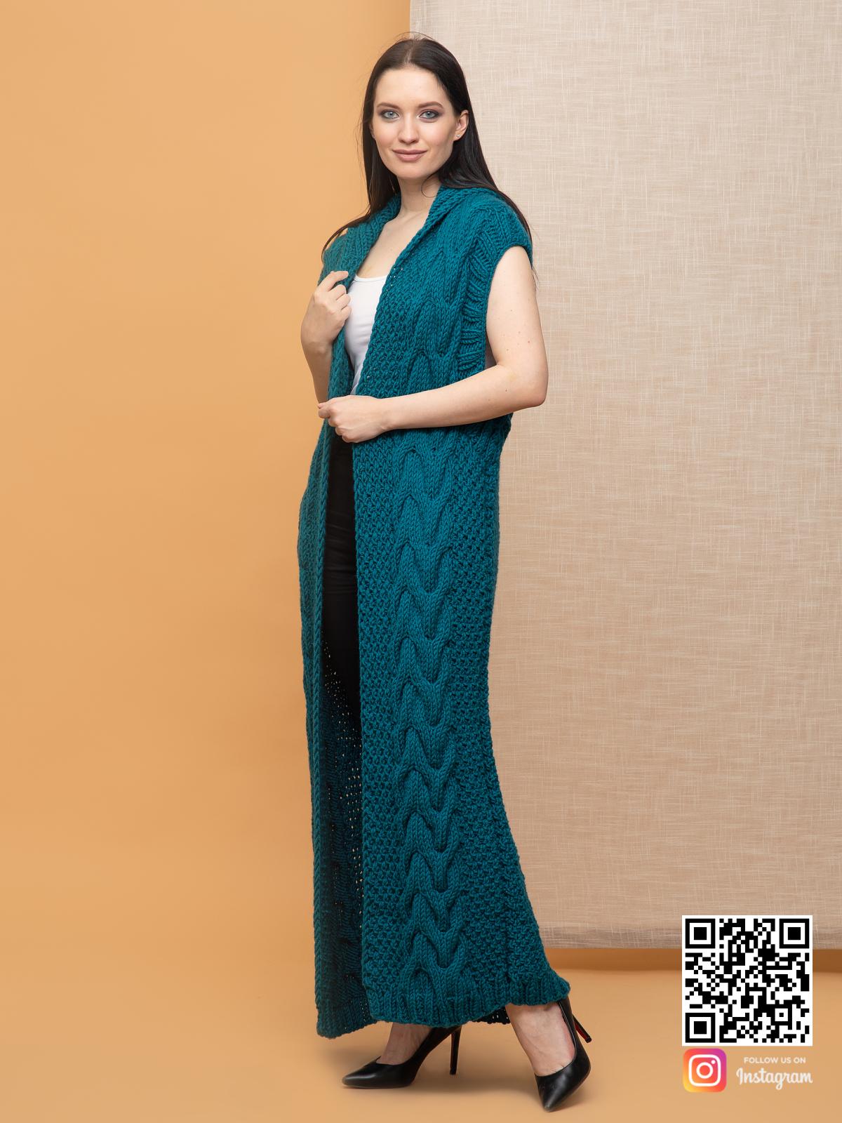 На фотографии женский длинный жилет с косами от Shapar, бренда вязаной одежды ручной работы в интернет-магазине связанных спицами вещей.