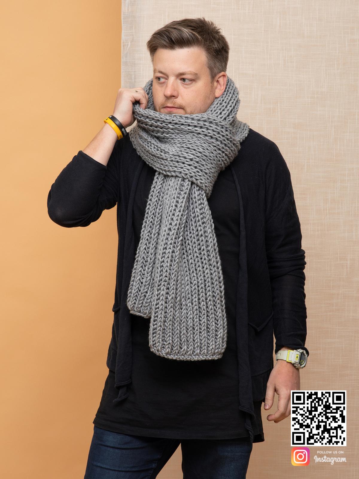 На фотографии серый шарф мужской от Shapar, бренда вязаной одежды ручной работы в интернет магазине связанных спицами вещей.
