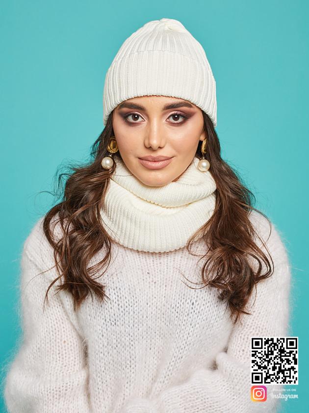 На фотографии белая шапка и снуд от Shapar, бренда вязаной одежды ручной работы в интернет-магазине связанных спицами вещей.