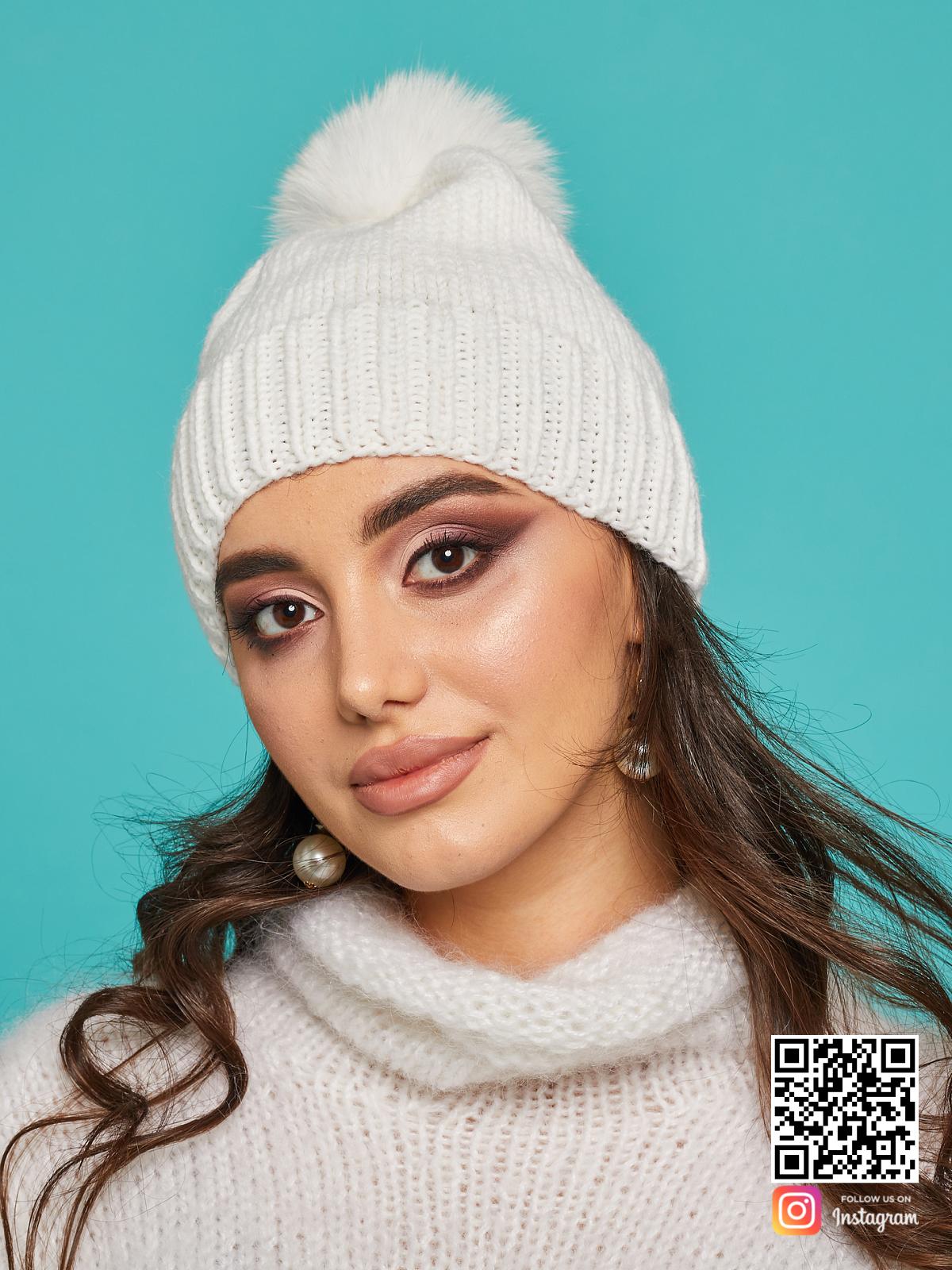 На фотографии белая шапка с помпоном от Shapar, бренда вязаной одежды и головных уборов ручной работы в интернет-магазине связанных спицами вещей.