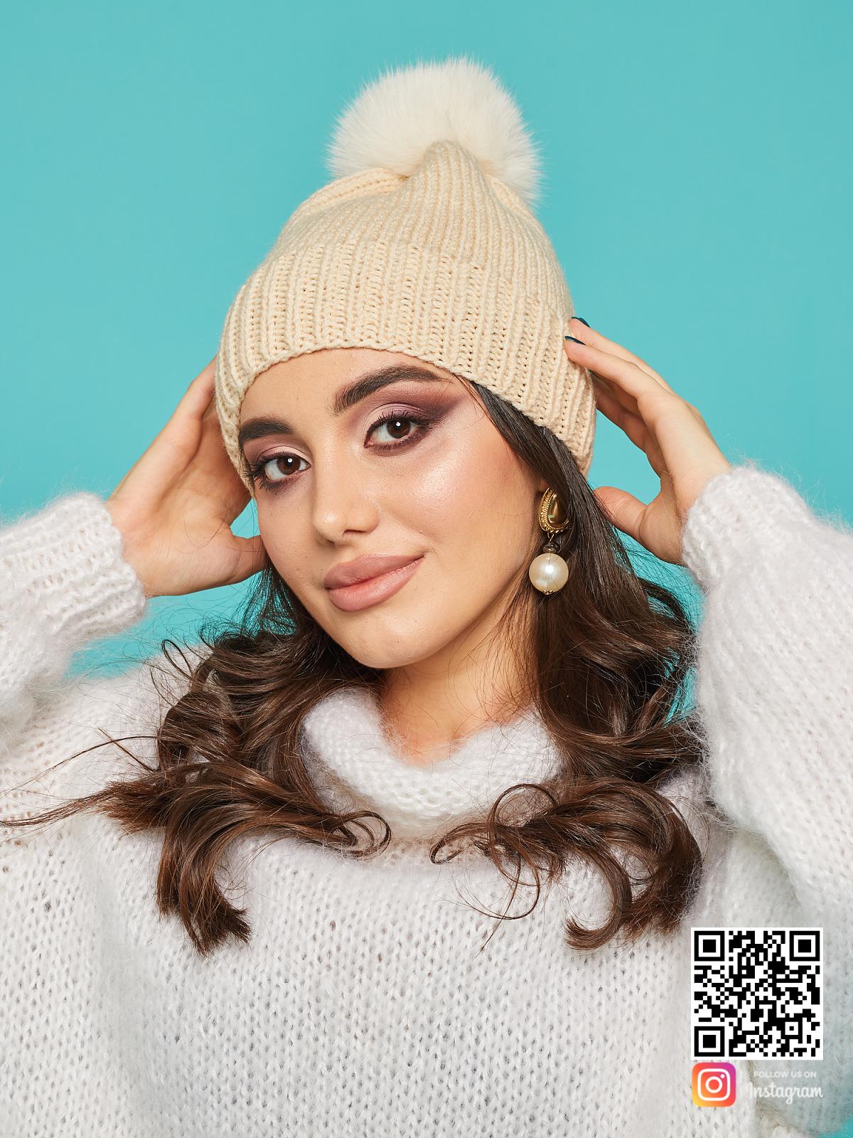 На пятой фотографии бежевая шапка с помпоном из меха скандинавского песца от Shapar, бренда вязаной одежды и головных уборов ручной работы в интернет-магазине связанных спицами вещей.