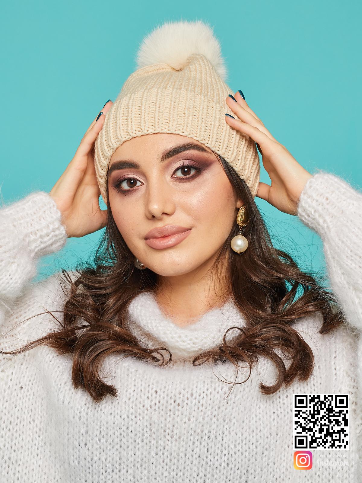 На фотографии бежевая шапка с помпоном от Shapar, бренда вязаной одежды и головных уборов ручной работы в интернет-магазине связанных спицами вещей.