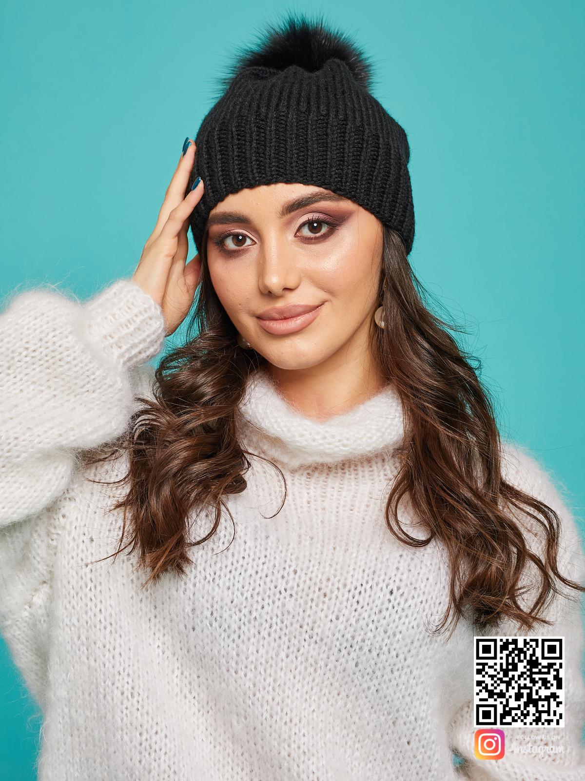 На фотографии черная шапка с помпоном от Shapar, бренда вязаной одежды и головных уборов ручной работы в интернет-магазине связанных спицами вещей.