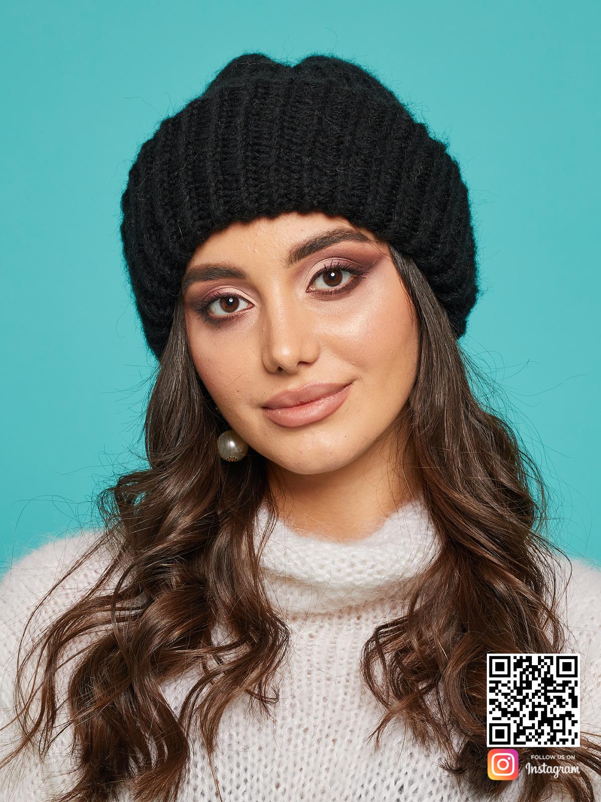 На фотографии черная вязаная шапка женская от Shapar, бренда одежды и головных уборов ручной работы в интернет-магазине связанных спицами вещей.